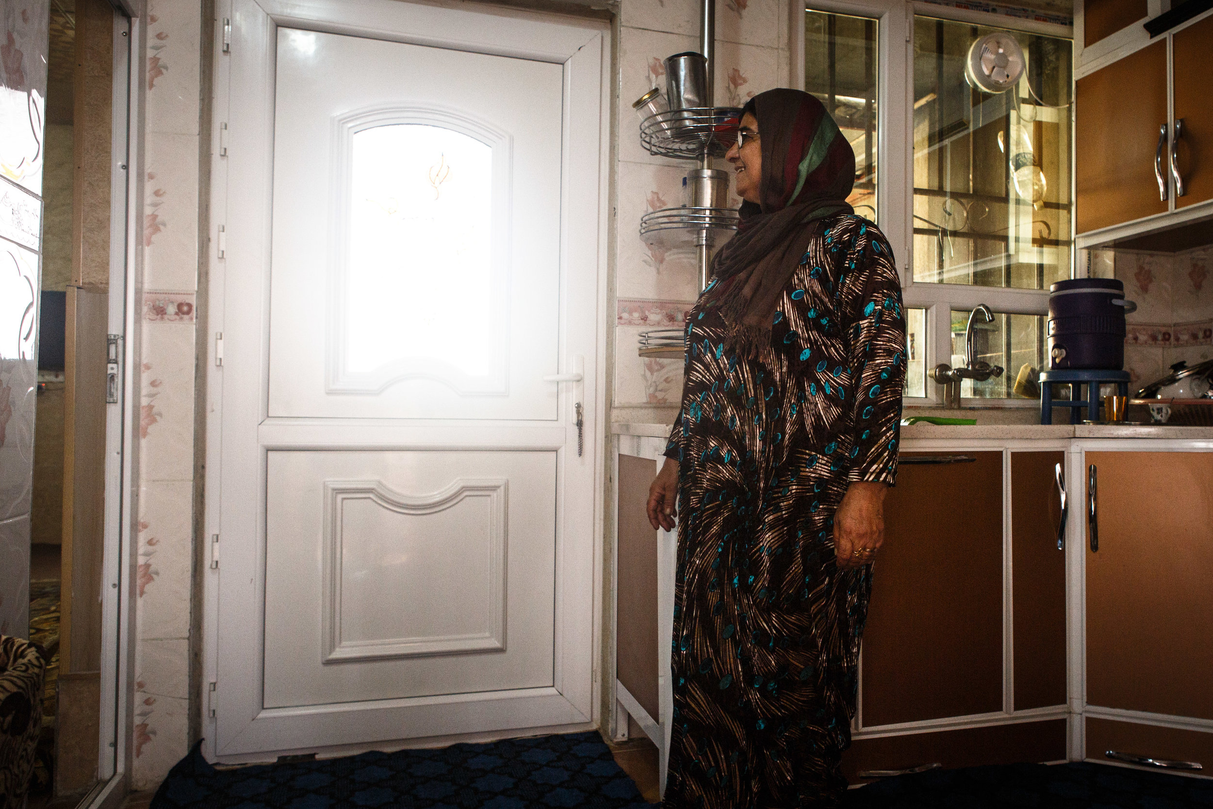 The wife of Abdul Kadr Muhammed looks out the window of the kitchen.