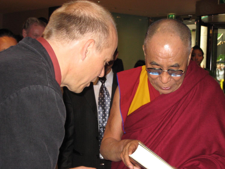 De Dalai Lama neemt vol interesse het boek  Dalai Lama, wijze van deze tijd van Bert van Baar in ontvangst bij zijn bezoek aan Amsterdam in 2009.