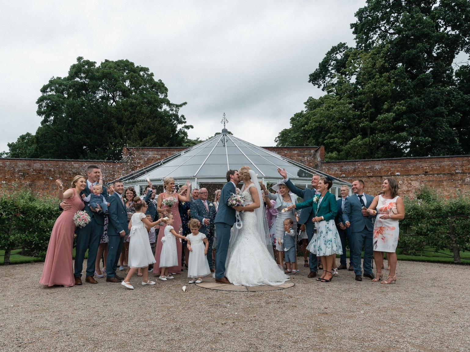 Guests throwing confetti over bride and groom at combermere abbey