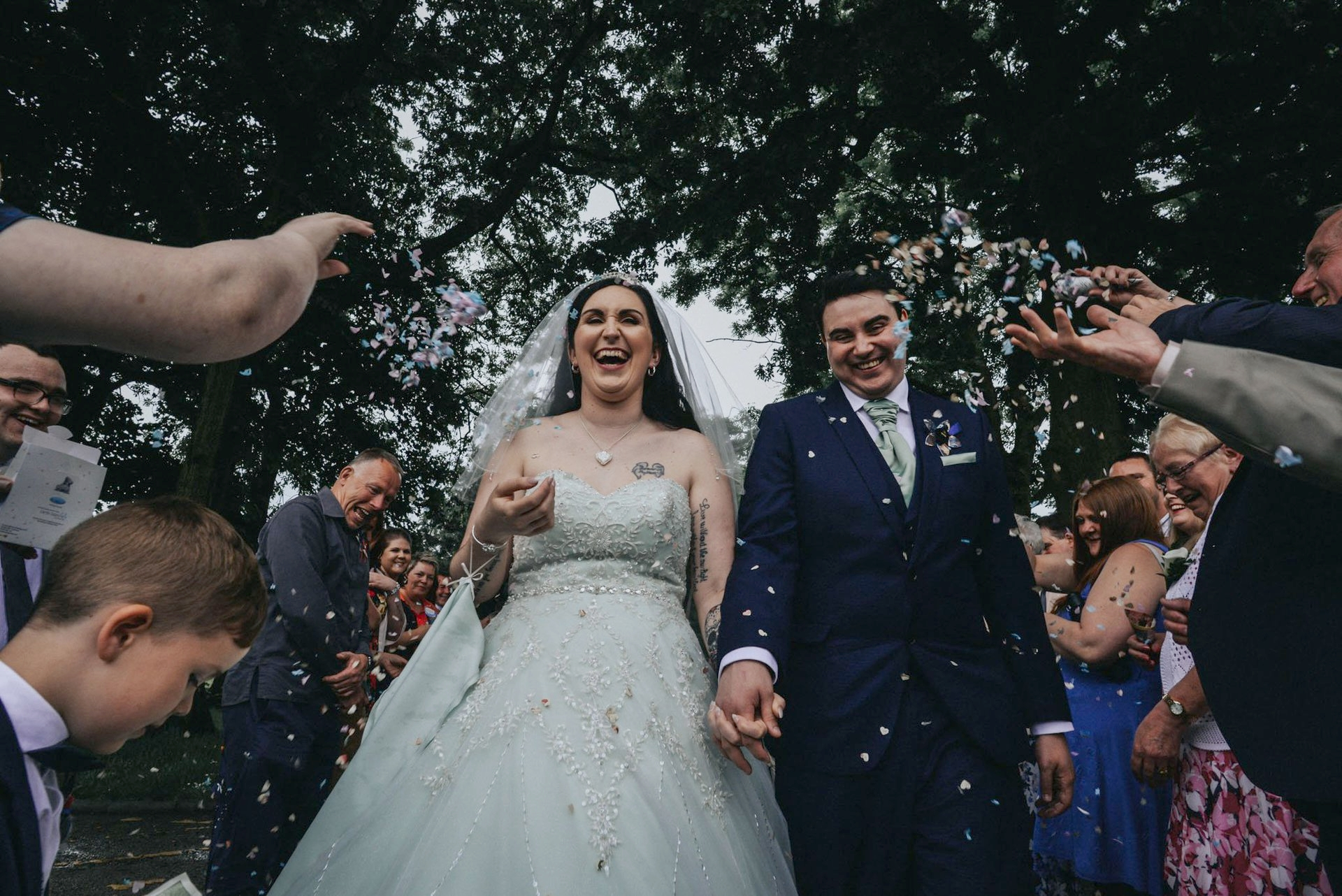 bride and groom laugh hysterically during their confetti images for their superhero wedding in Manchester - Manchester wedding photographer