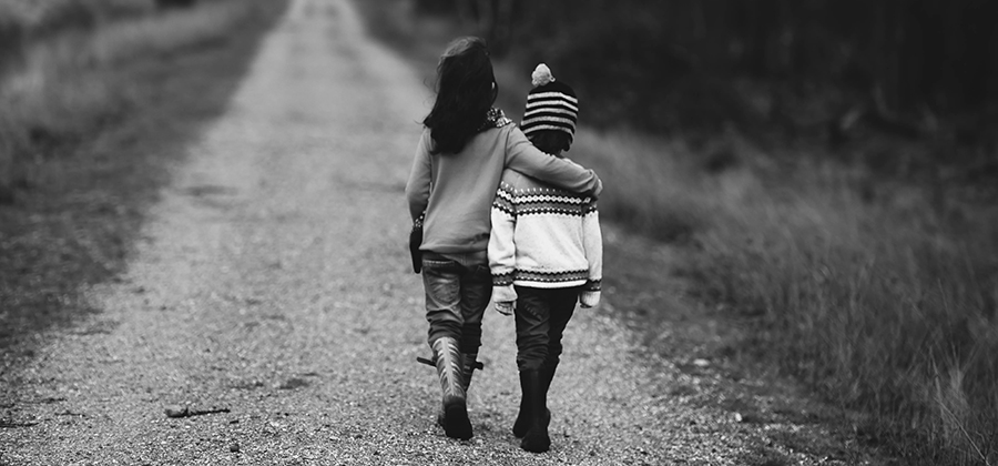 2 children walking down a dirt road with one arm around the other.