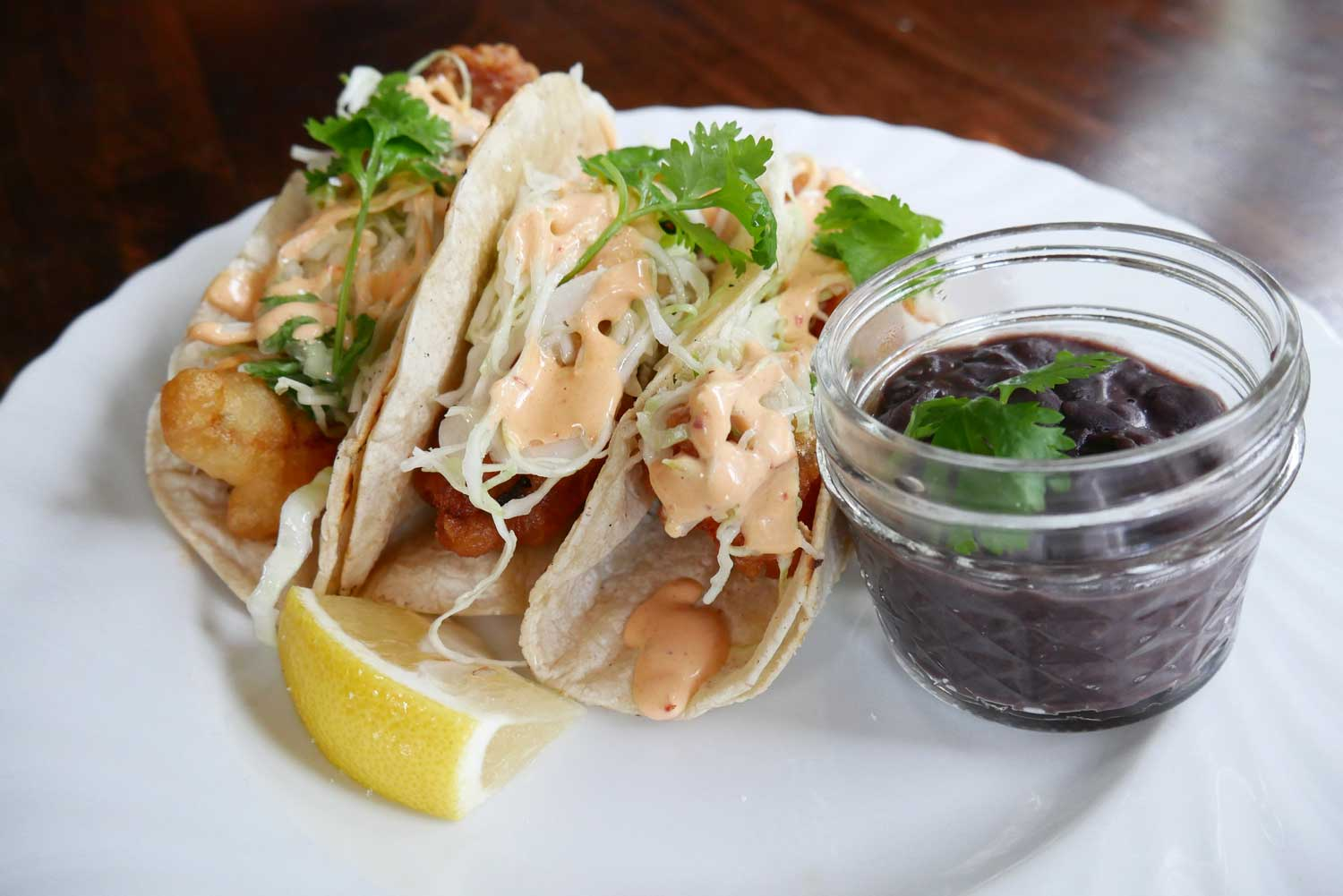 Crispy fish tacos with cilantro slaw and chipotle aioli. Served with a side of black beans