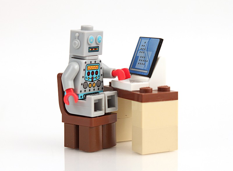 A Lego robot sitting at a computer.