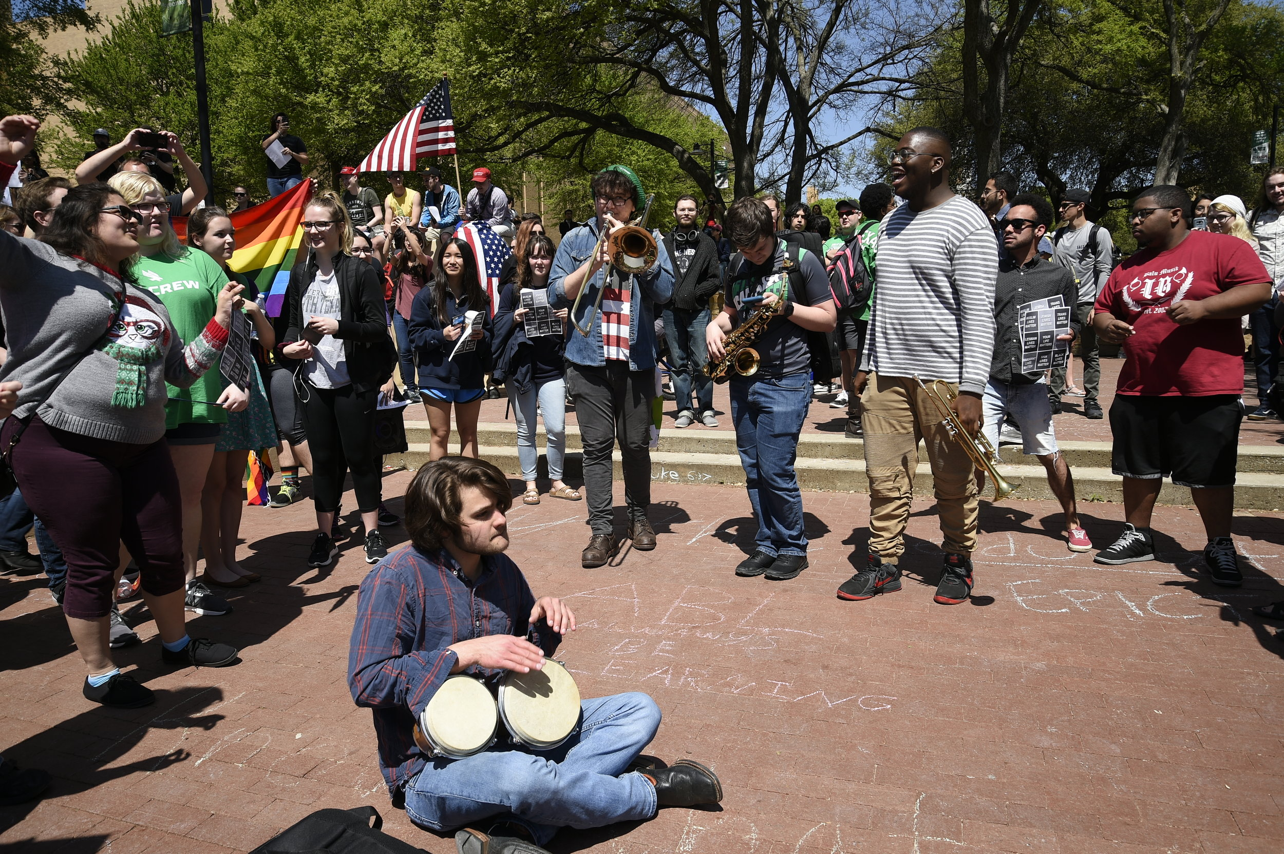 UNT students play music around a circle during a protest.