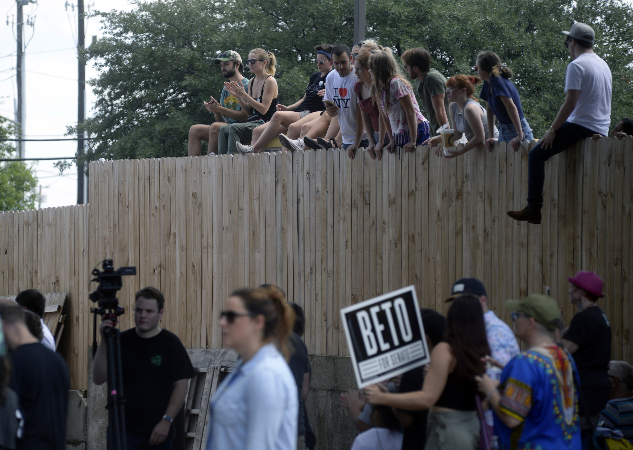 Denton residents look over a fence near Golden Chick adjacent to Backyard on Bell. When the bar/venue filled to capacity during a town hall event for Senate candidate Beto O'Rourke, locals were forced to find adjacent areas to listen to the rally. Jake King/DRC