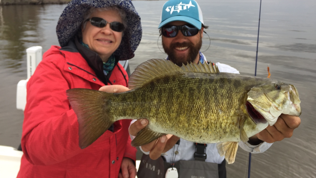 """Kathy worked a """"Roger Rig"""" out the back of the boat while her husband Gary threw topwater flies out the front. Both picked up fish including this one. Yes, that little hook on the 1/32 oz jighead can work on a big fish like this."""