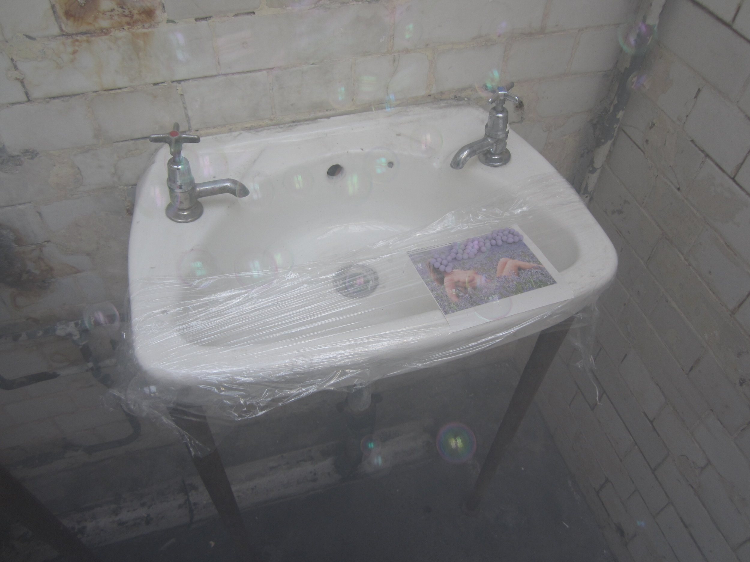 Lavender Lady Contagion (clean & safe)    – lavender felt bobbles, image of topless model in bluebell field from Hungarian newspaper, cling film, sink, smoke and bubbles in Victorian Gentlemen's toilet, Kennington, London, 2015
