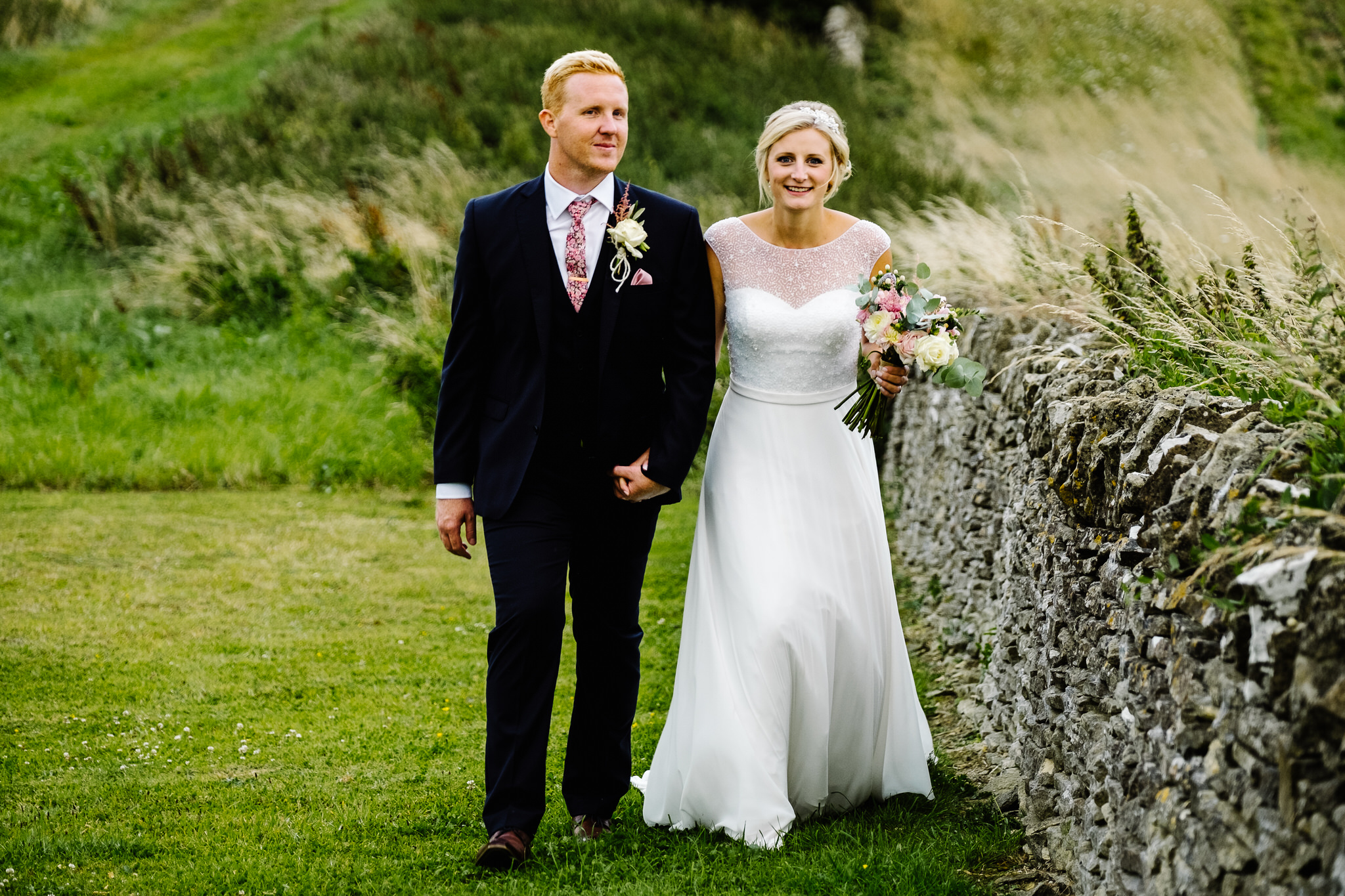 A bride and groom walking outside their wedding venue,  Cripps Stone Barn , Gloucestershire