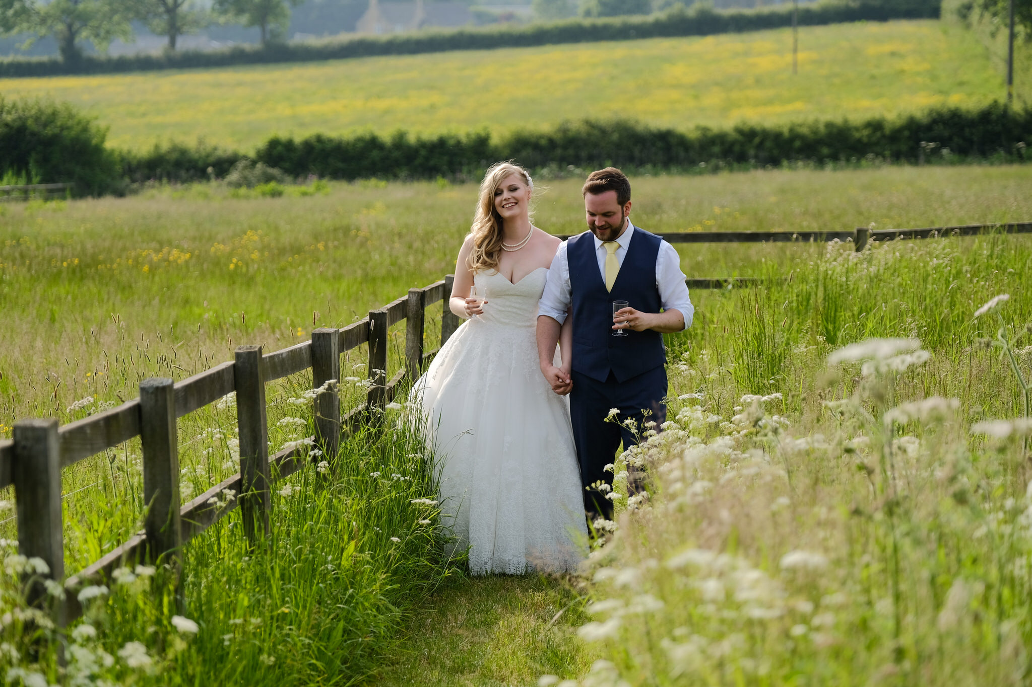 A bride and groom walking in the sun at  Hyde Barn Wedding Venue , Stow on the Wold