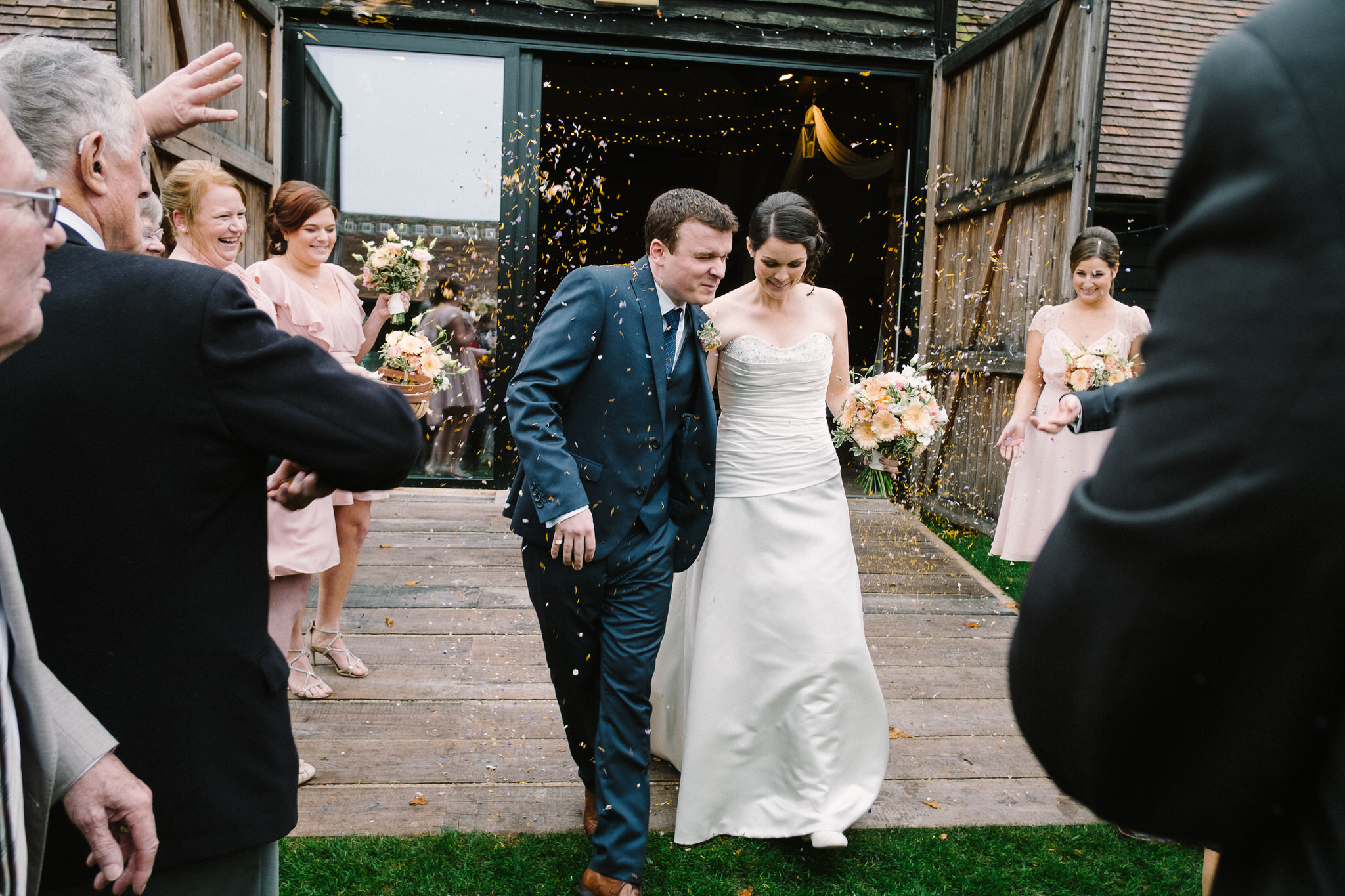 A bride and groom leaving their wedding ceremony at Lains Barn, Wantage, Oxfordshire