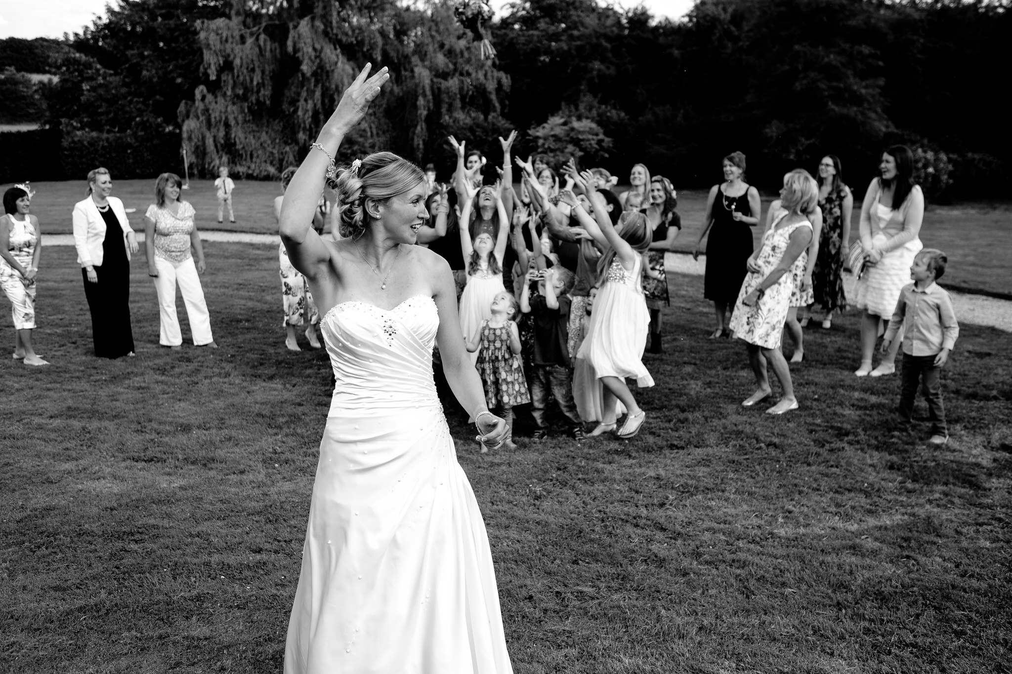 A bride tosses her bouquet at a wedding at Poundon House, Near Bicester Oxfordshire
