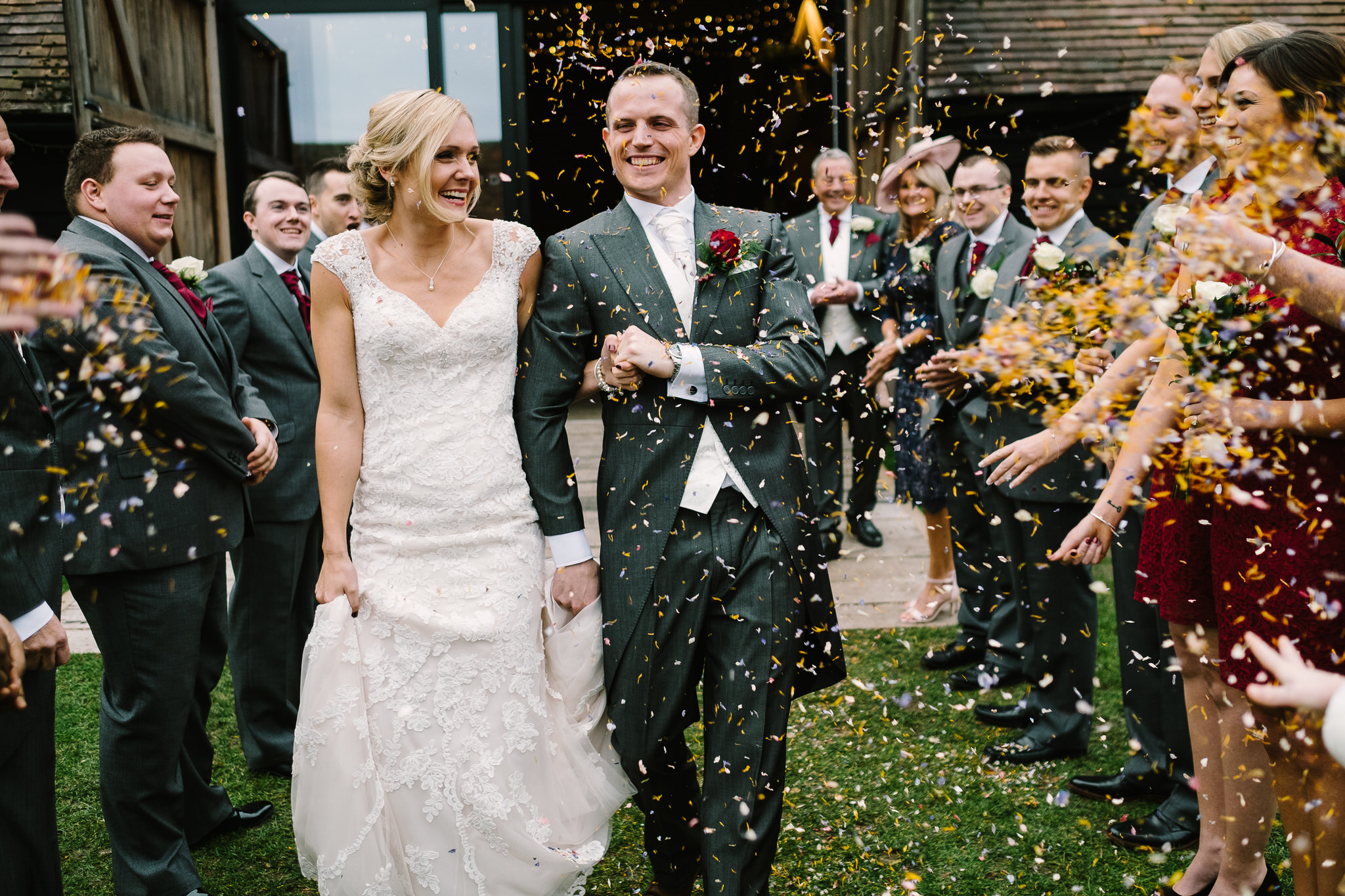The bride and groom in confetti outside Lains Barn Wedding Venue, Oxfordshire