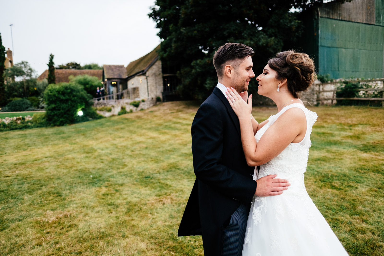 A bride and groom embrace outside Notley Tythe Barn, Buckinghamshire. Photo by Sam and Steve Photography