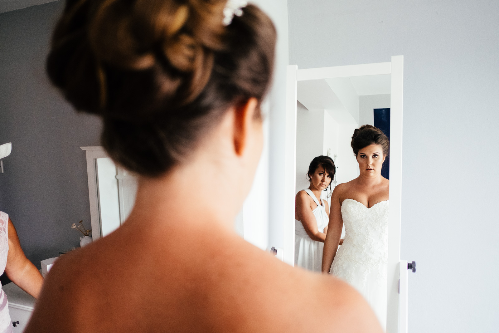 A bride checks her reflection in a mirror. Photo by Sam and Steve Photography