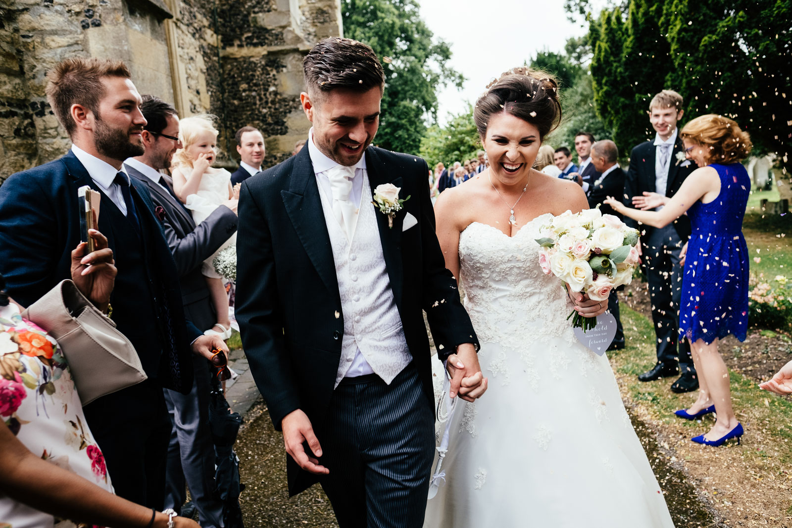 A bride and groom in confetti at Chinnor Church. Photo by Sam and Steve Photography