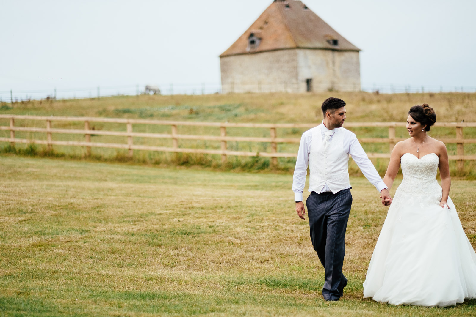 A bride and groom walking outside Notley Tythe Barn wedding Venue