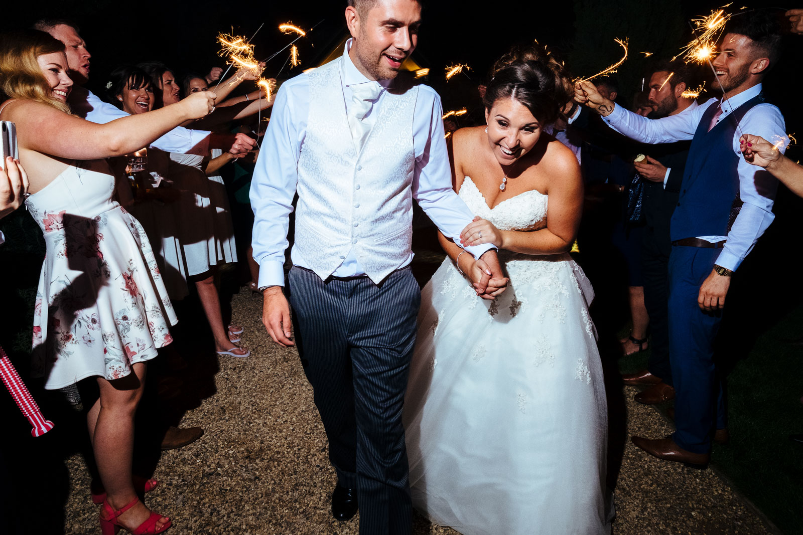 A bride and groom surrounded by sparklers at Notley Tythe Barn Wedding Venue
