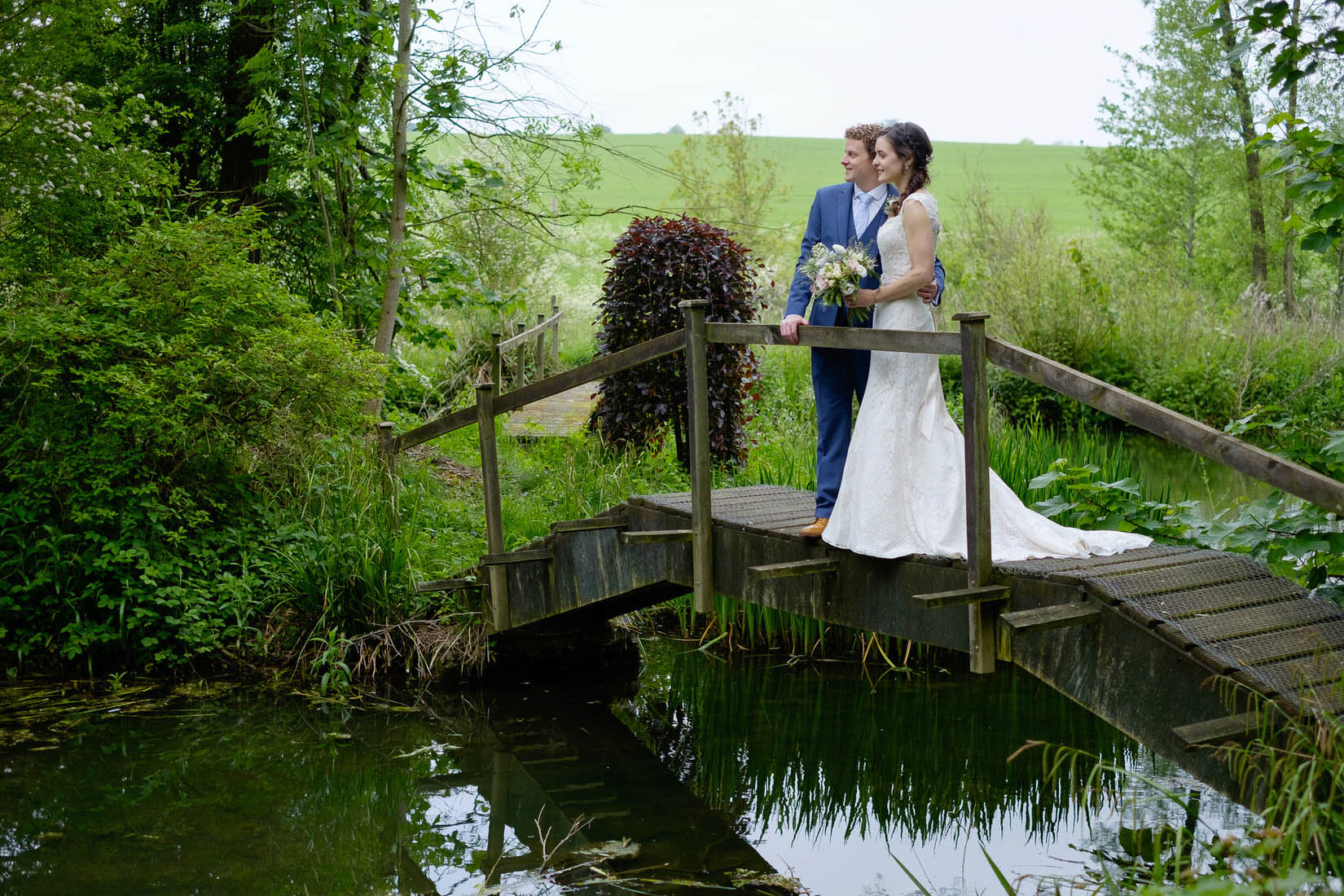 A bride and groom on a bridge over a lake at Great Barn Wedding Venue, Aynho. Photo by Sam and Steve Photography