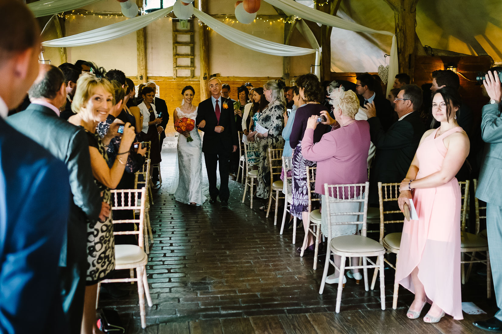 A bride and her father approaching a groom at Lains Barn Wedding Venue Oxfordshire