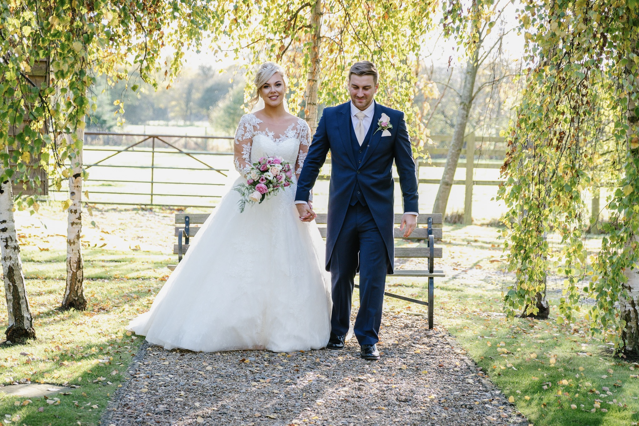 A bride and groom walking in the Autumn sun after their wedding at The Tythe Barn, Bicester