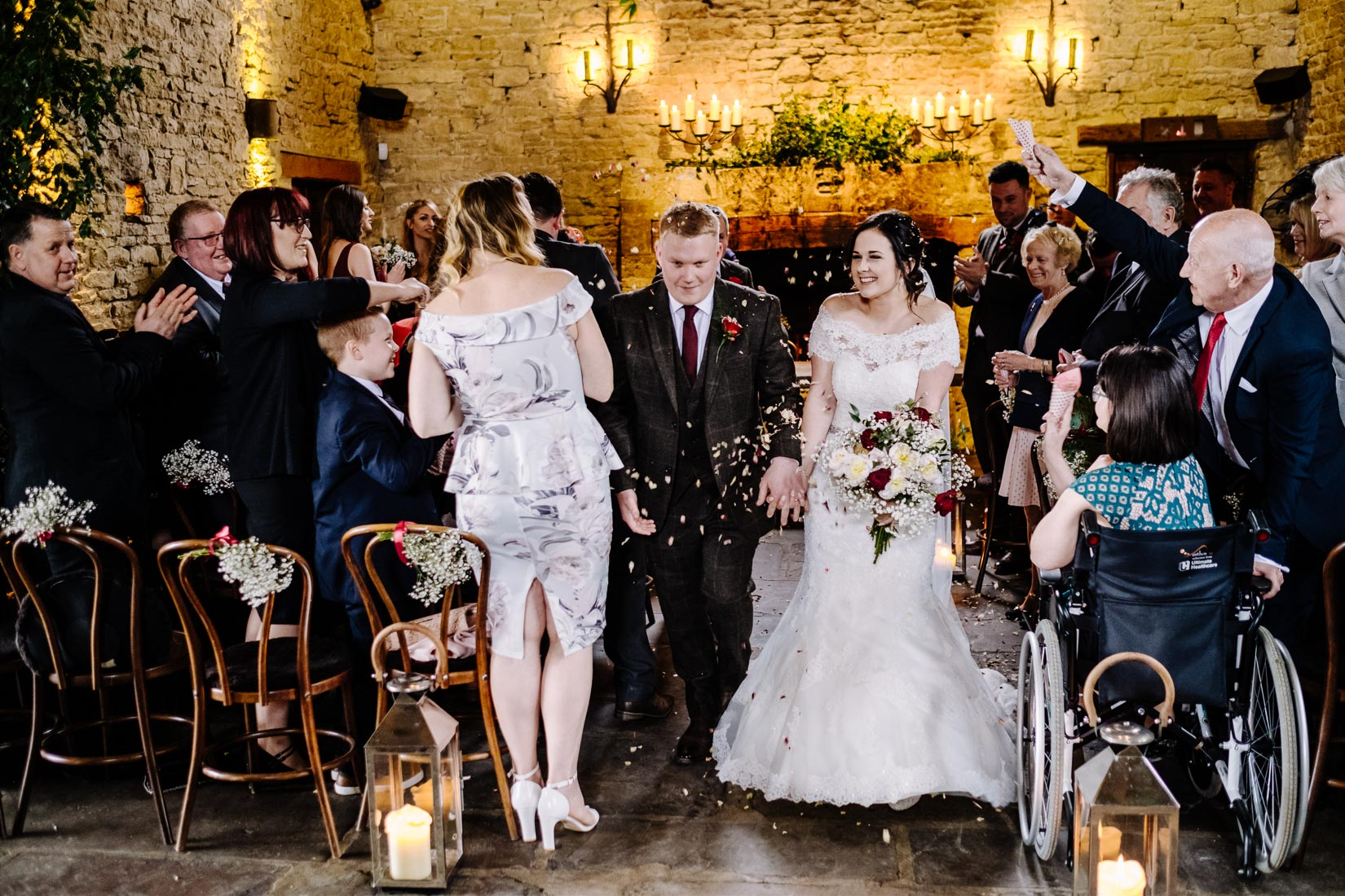 A Bride and Groom covered in confetti leaving their wedding at the Bay Tree, Burford.