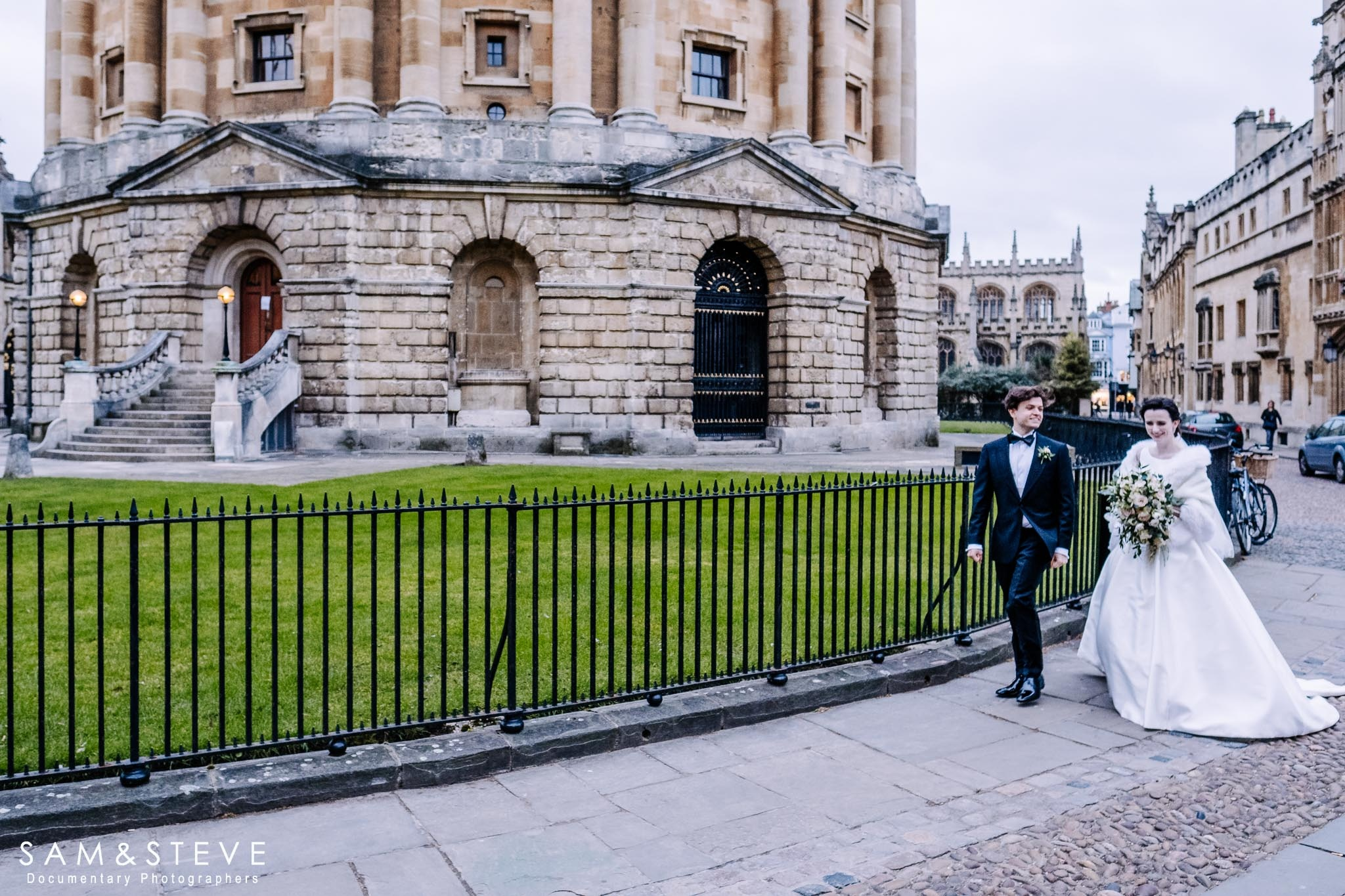 a bride and groom walking by the Radcliffe Camera, Oxford