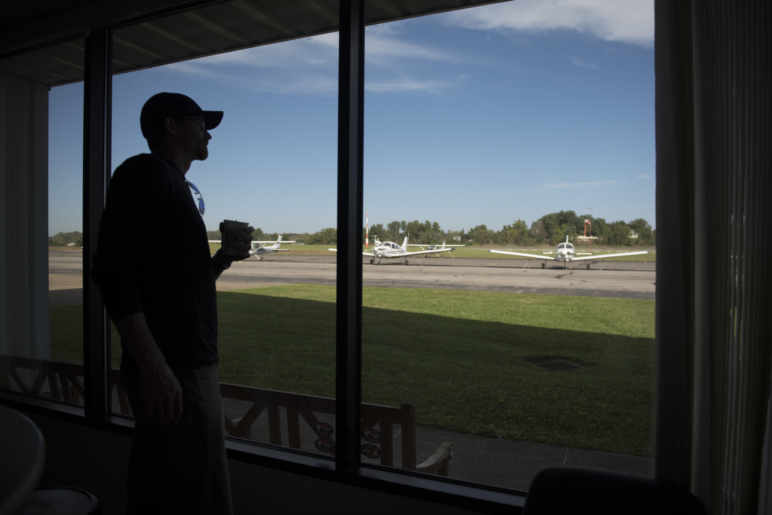 Flight instructor Eric Lee watches planes take off through the window of the training center at Gordon K. Bush airport on Sept. 24, 2017.