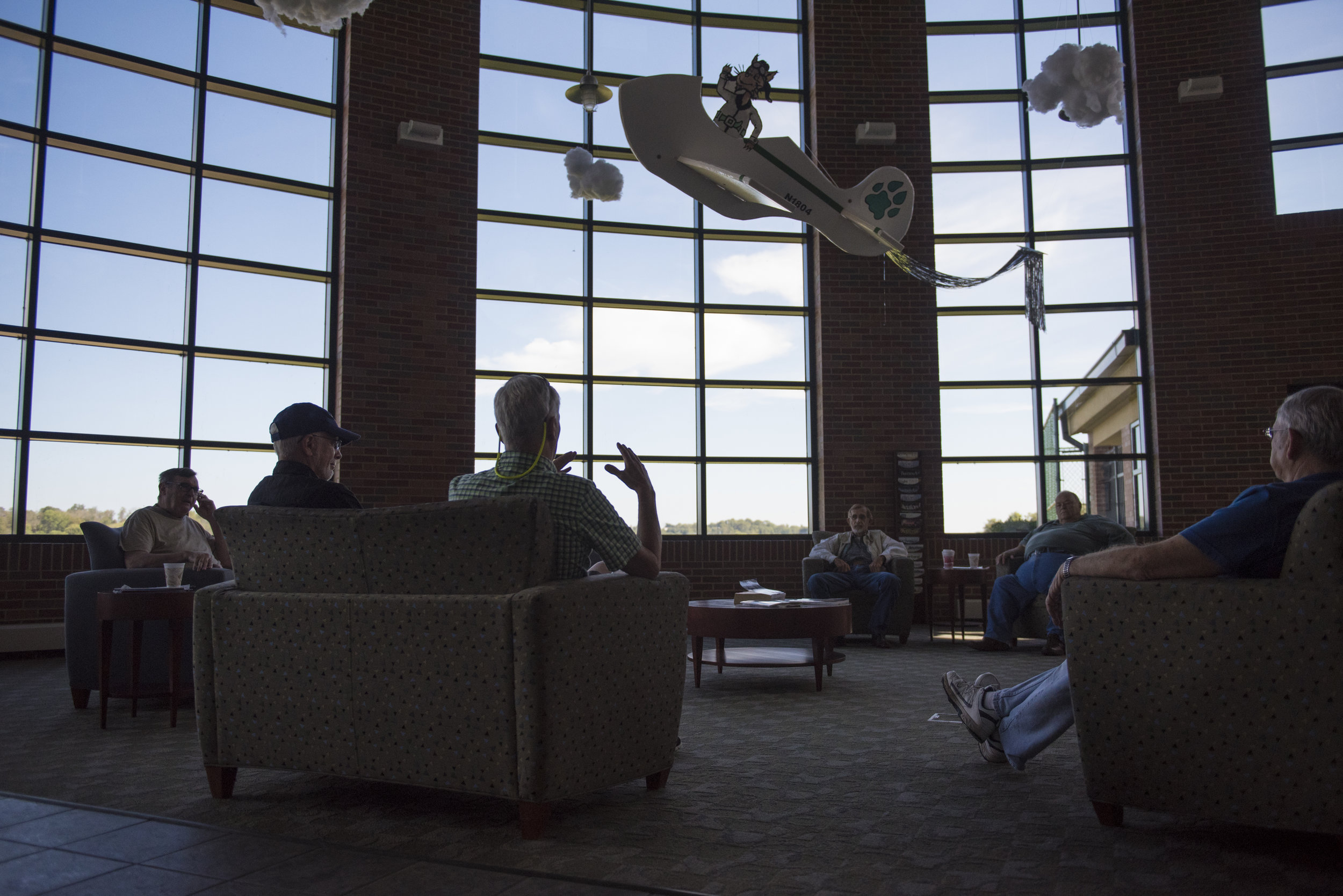 (From left to right) Rich Beckmell, Charlie Dorsey, Bryan Branham, Dave Weks, Phil Laughlin and Virgil Reeves sit in the terminal at Gordon K. Bush on Sept. 24, 2017. Every weekend they hang out, discuss flying and reminisce about the past while enjoying coffee and donuts.
