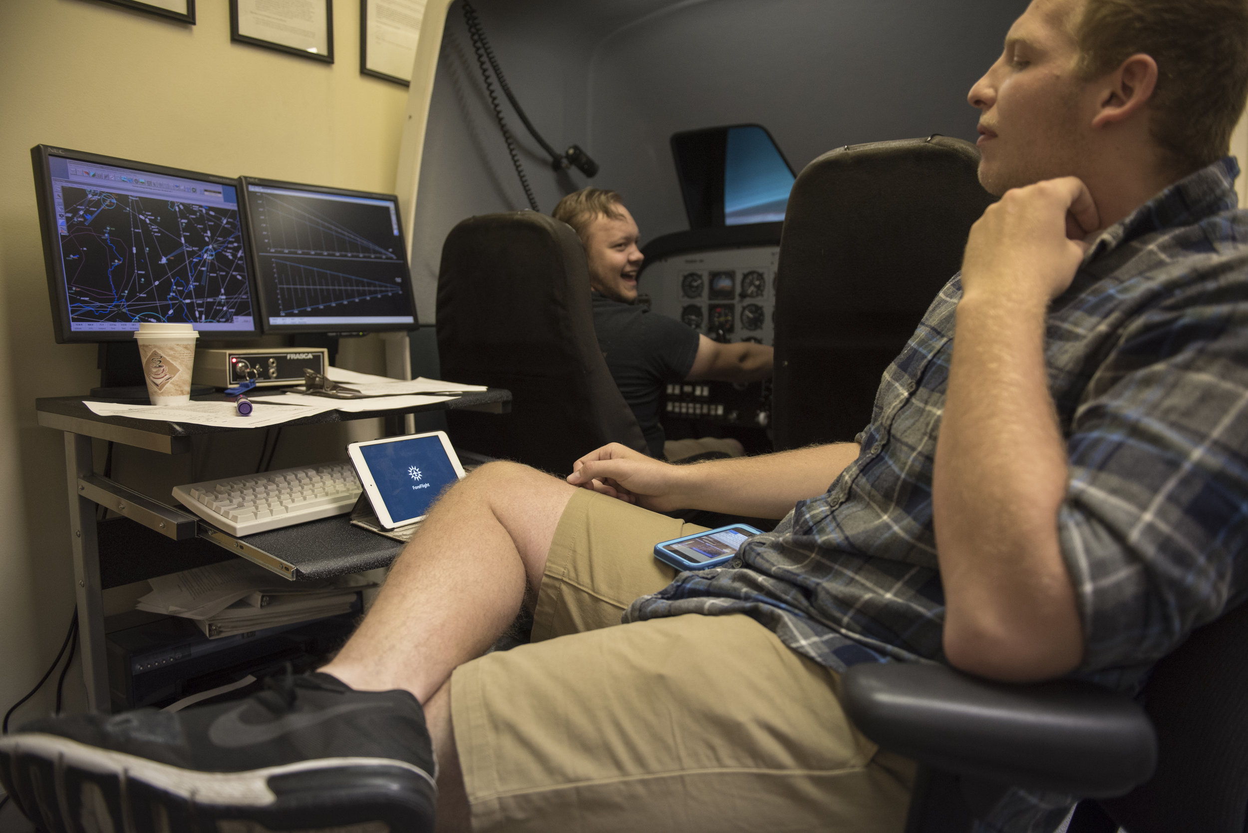Flight instructor Michael Popo (right) instructs Ohio University sophomore Jacob O'Dea in the simulator on Sept. 23, 2017. Popo and O'Dea spent five hours in the simulator getting caught up on lessons.