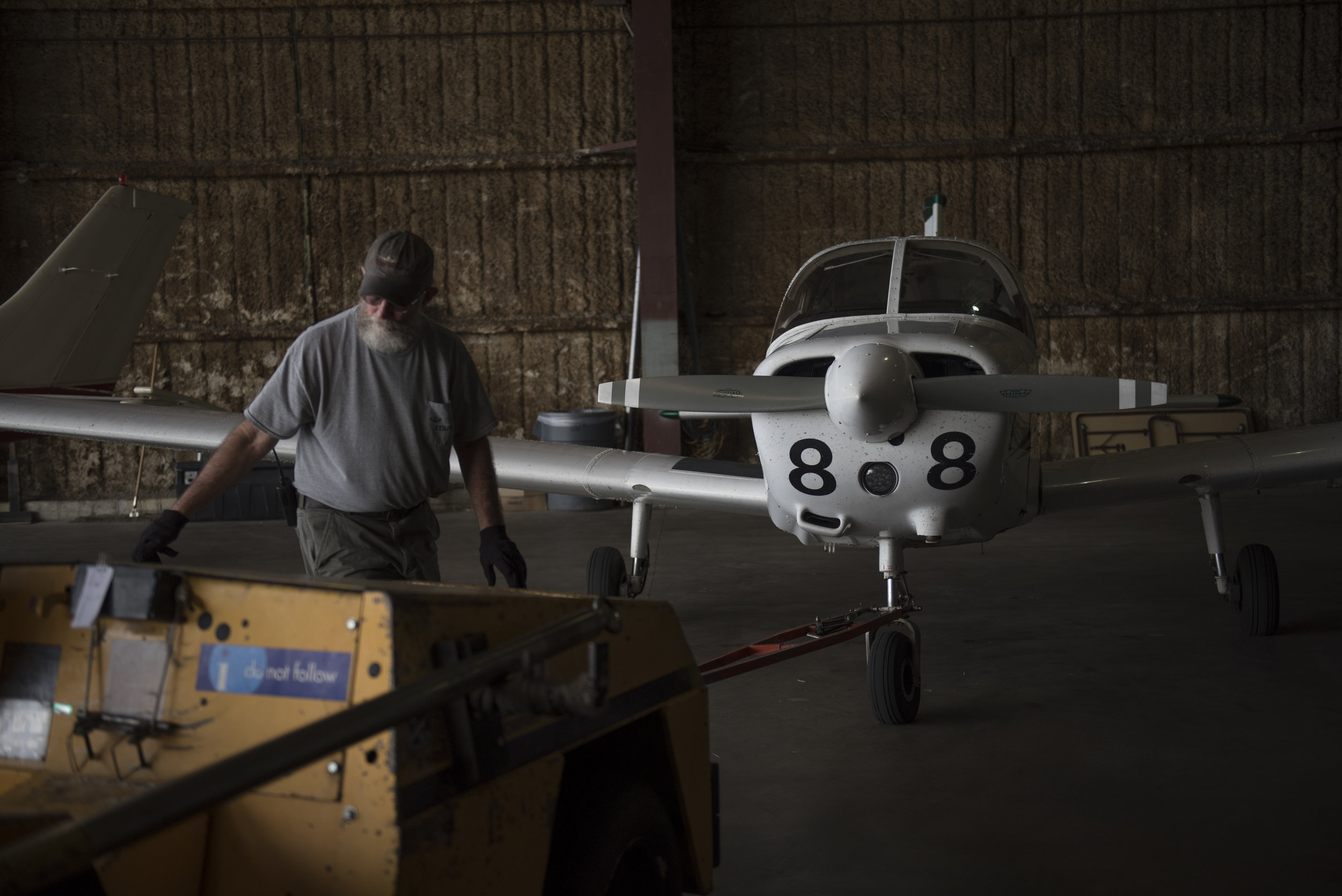 Lineman Bob Black moves one of the Ohio University airplanes out of the hangar in preparation for student use on Sept. 20, 2017.