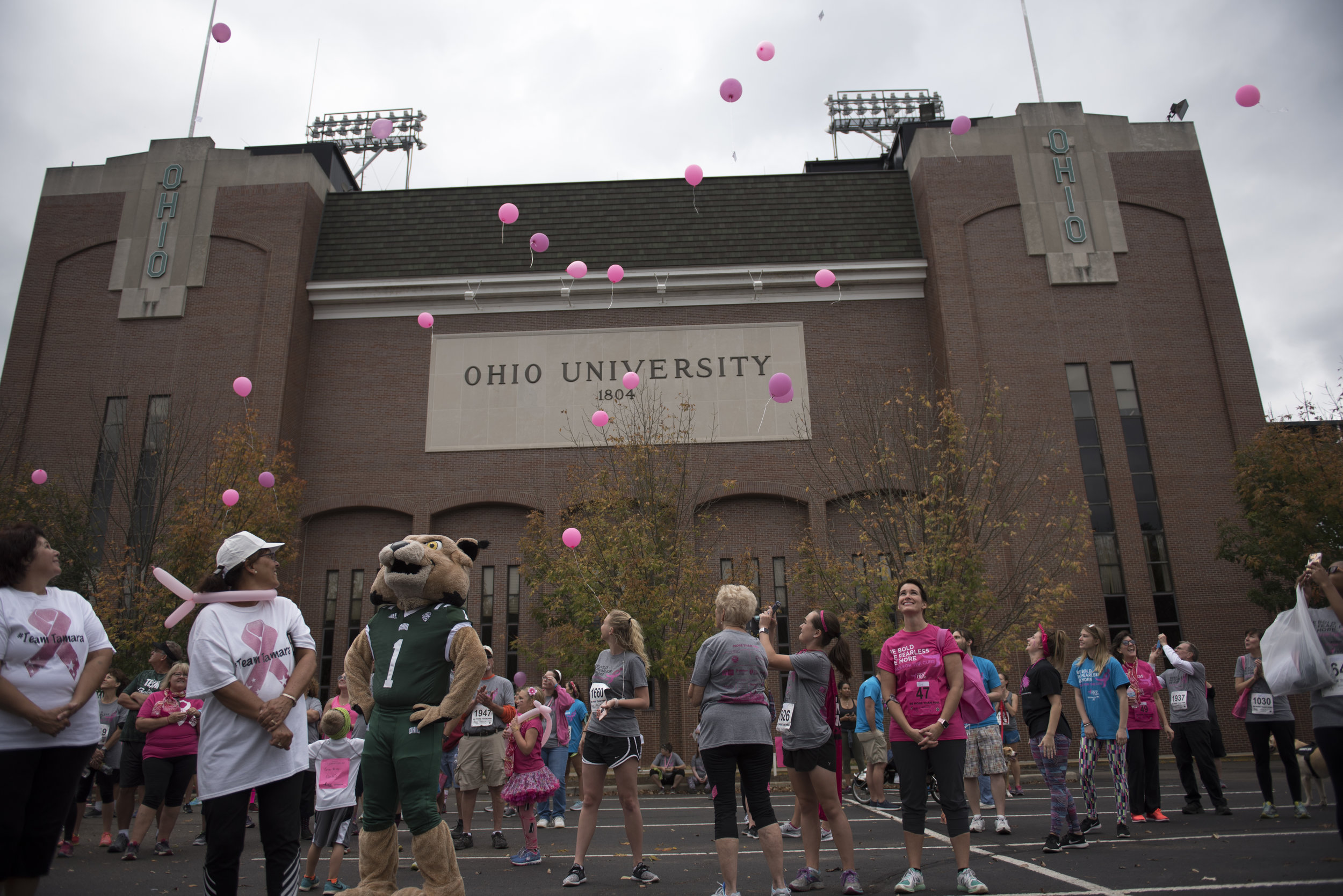 Runners watch pink balloons float up to the sky outside Peden Stadium before the start of the Race for the Cure on Oct. 15, 2017 in Athens, Ohio.