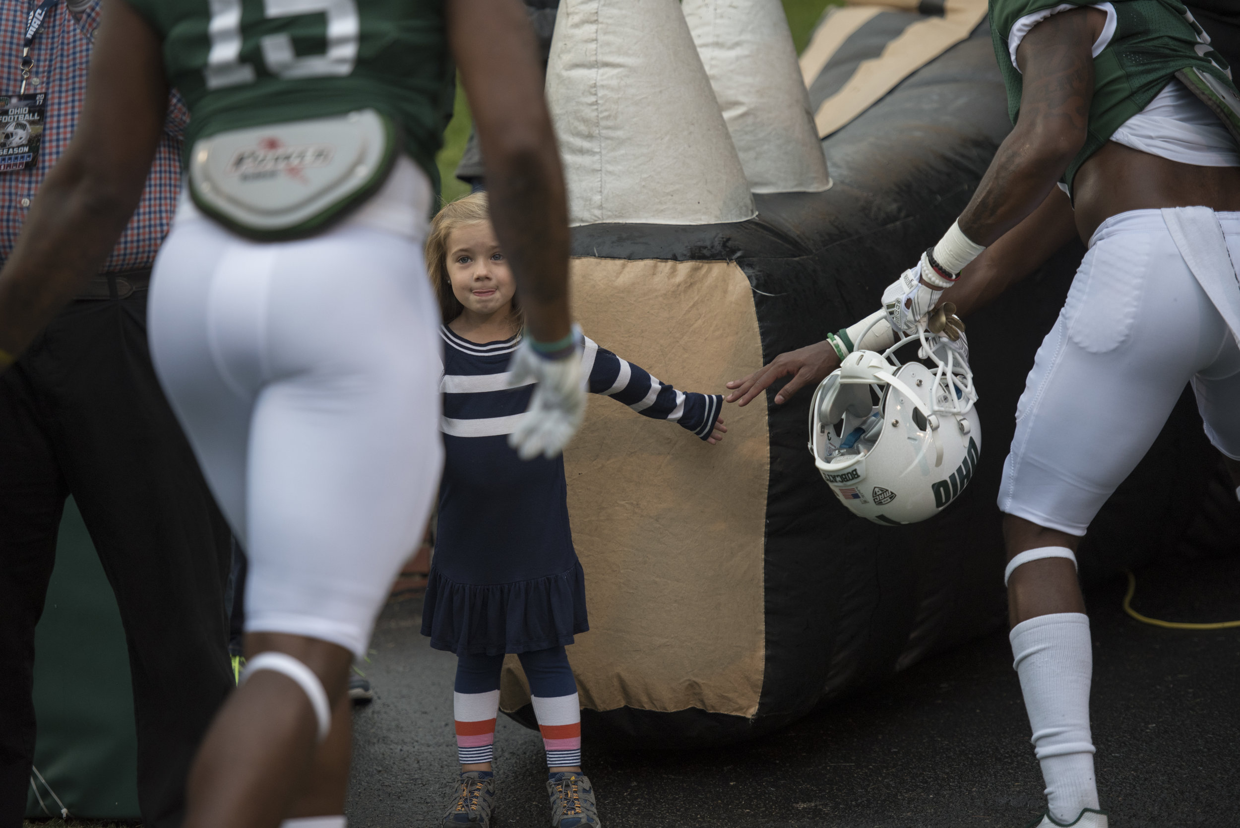 Penelope Carroll, age 4, high fives Ohio University football players as they go back into the tunnel on Sept. 2, 2017 during the home football game against Hampton University.