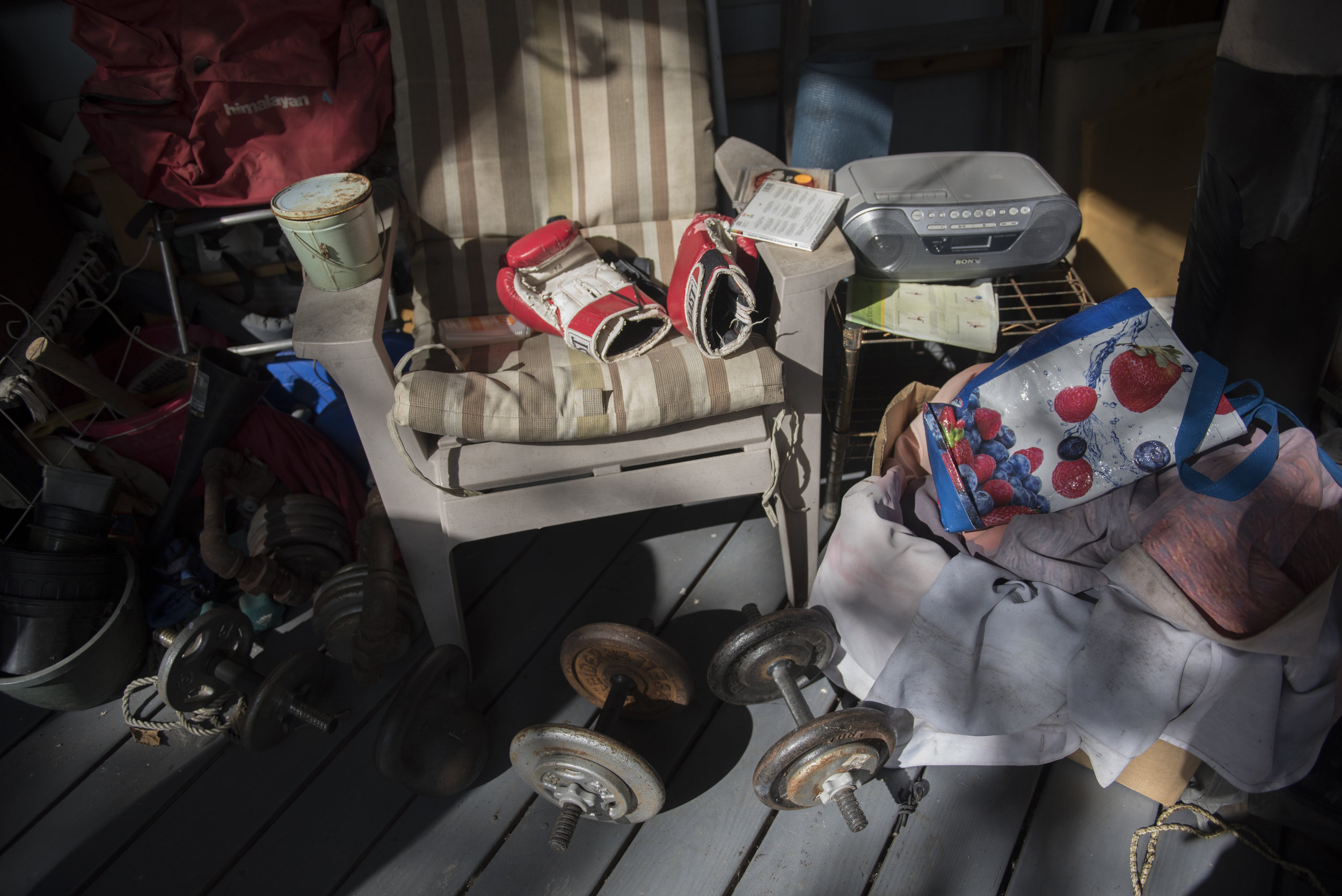 Patrick McGee's boxing gloves and weights lie out on his back porch on Sept. 3, 2017 in Athens, Ohio. To keep in shape, McGee rides a workout bike, lifts weights and boxes with a punching bag.