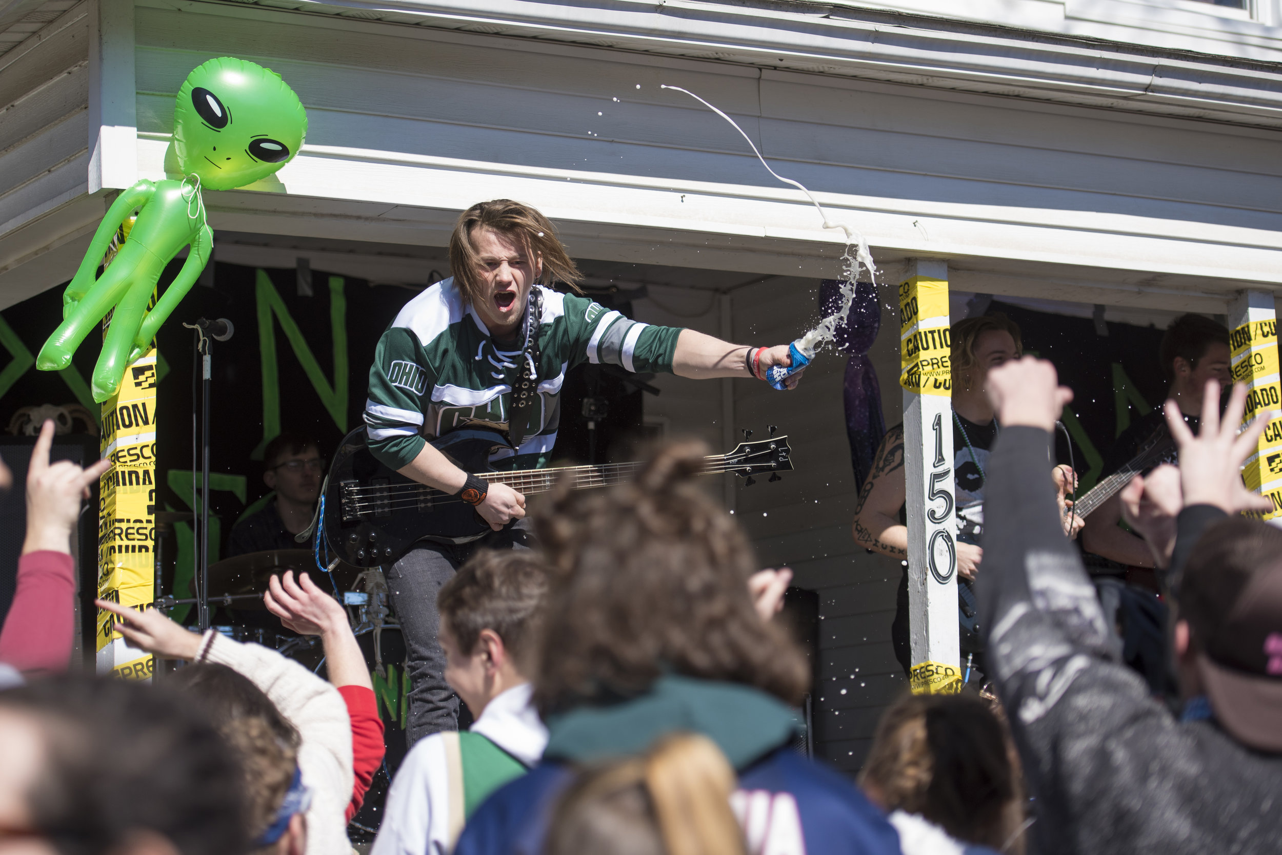 A member of the local band, Do Not Recessitate, throws a beer into the crowd during Mill Fest on March 3, 2018 in Athens, Ohio.
