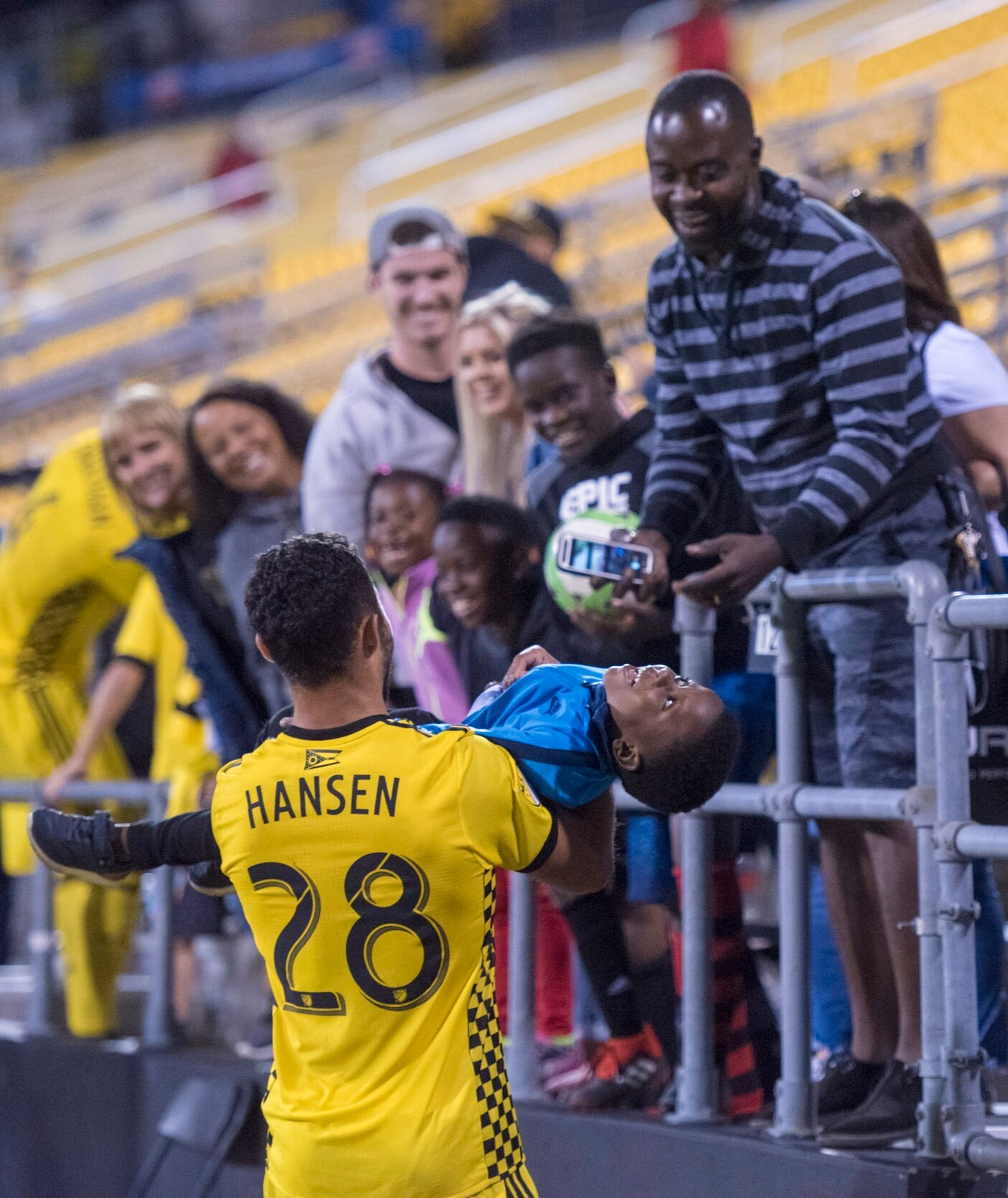 Columbus Crew forward Niko Hansen carries a child back to his family after the child jumped the barrier surrounding the field following the game against the Colorado Rapids.