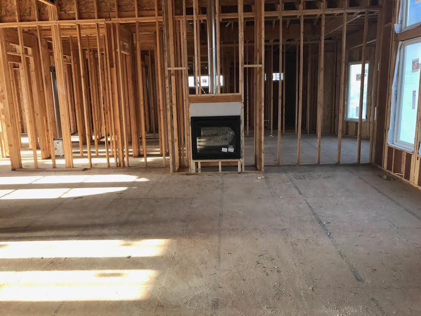 Standing at the back of the living room looking towards fireplace wall. The fireplace will be gray colored stone floor to ceiling. There will also be built in shelves on either side of the fireplace.