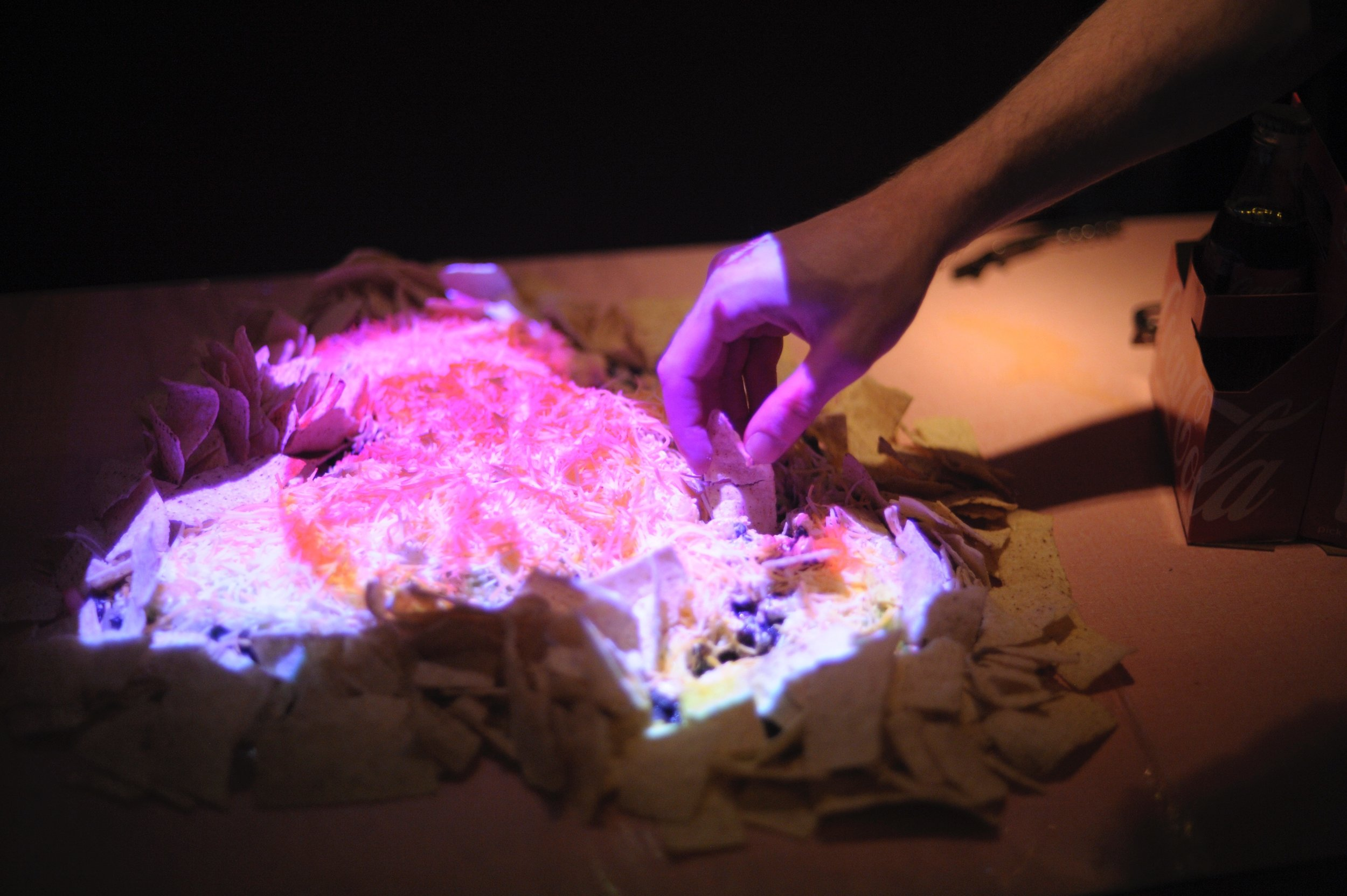 Video Nachos: projection of pizza zooming into pizza ad infinitum onto taco salad. Presented as an appetizer to a Synesthesia cabaret in homage to the magnitude of chefs loving taco salad and pizza.