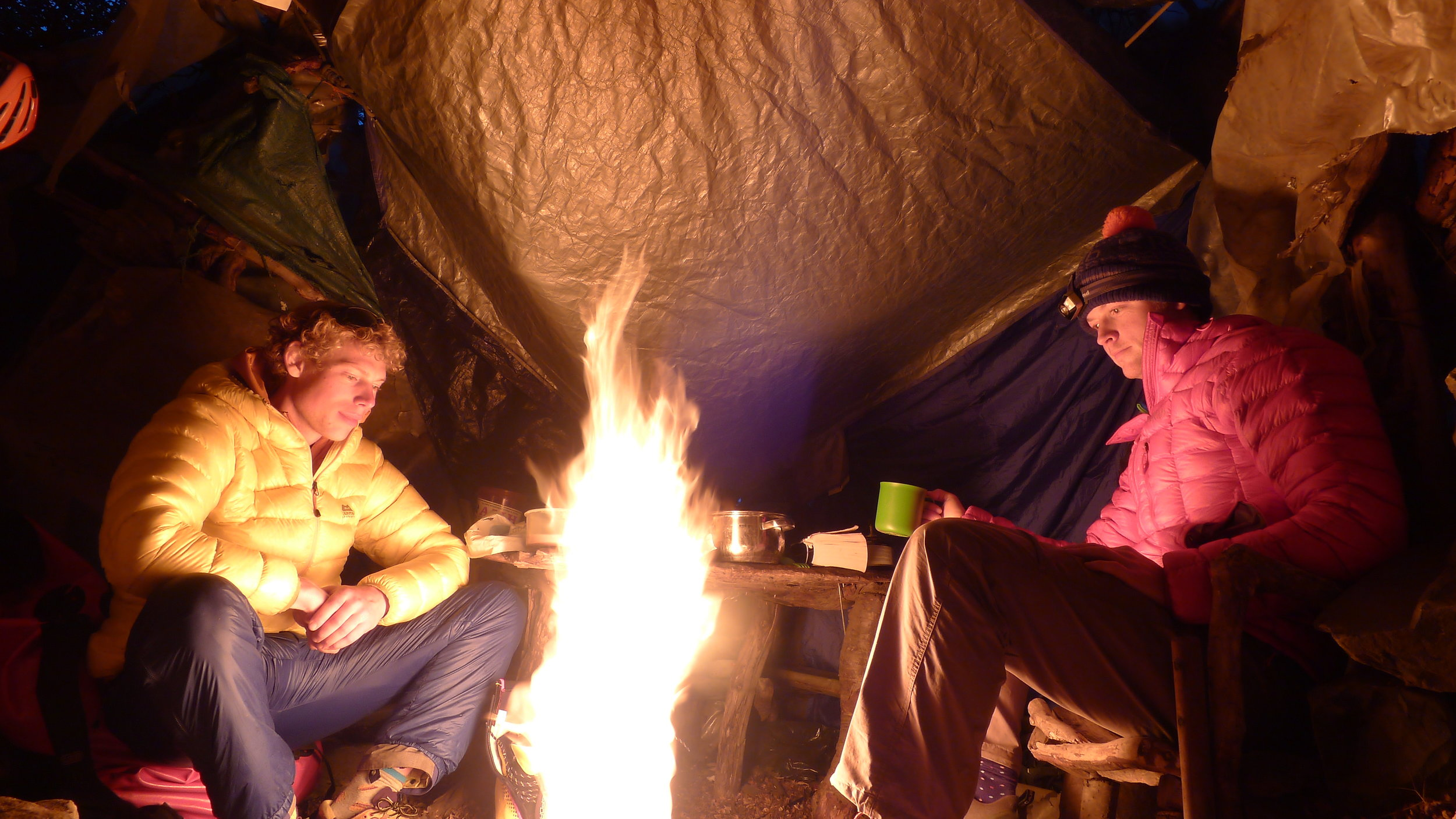 Calum and I look into the warmth of our MSR Whisperlite stove in the 'Trash Shack' - our Base Camp in Torres Del Paine, Chile. It wasn't the best way to cook, but it sure kept us warm!
