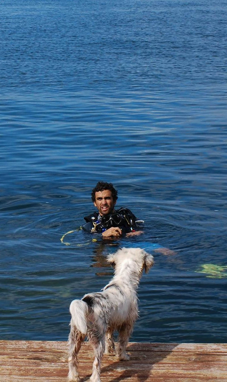 Alex awaits his open water dive student during the confined water portion of the course, while Scratchy the dog supervises Alex.