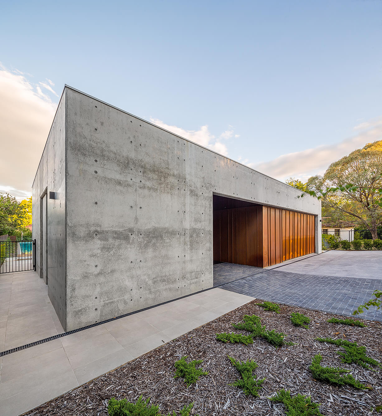 off form concrete house facade with rusted garage door