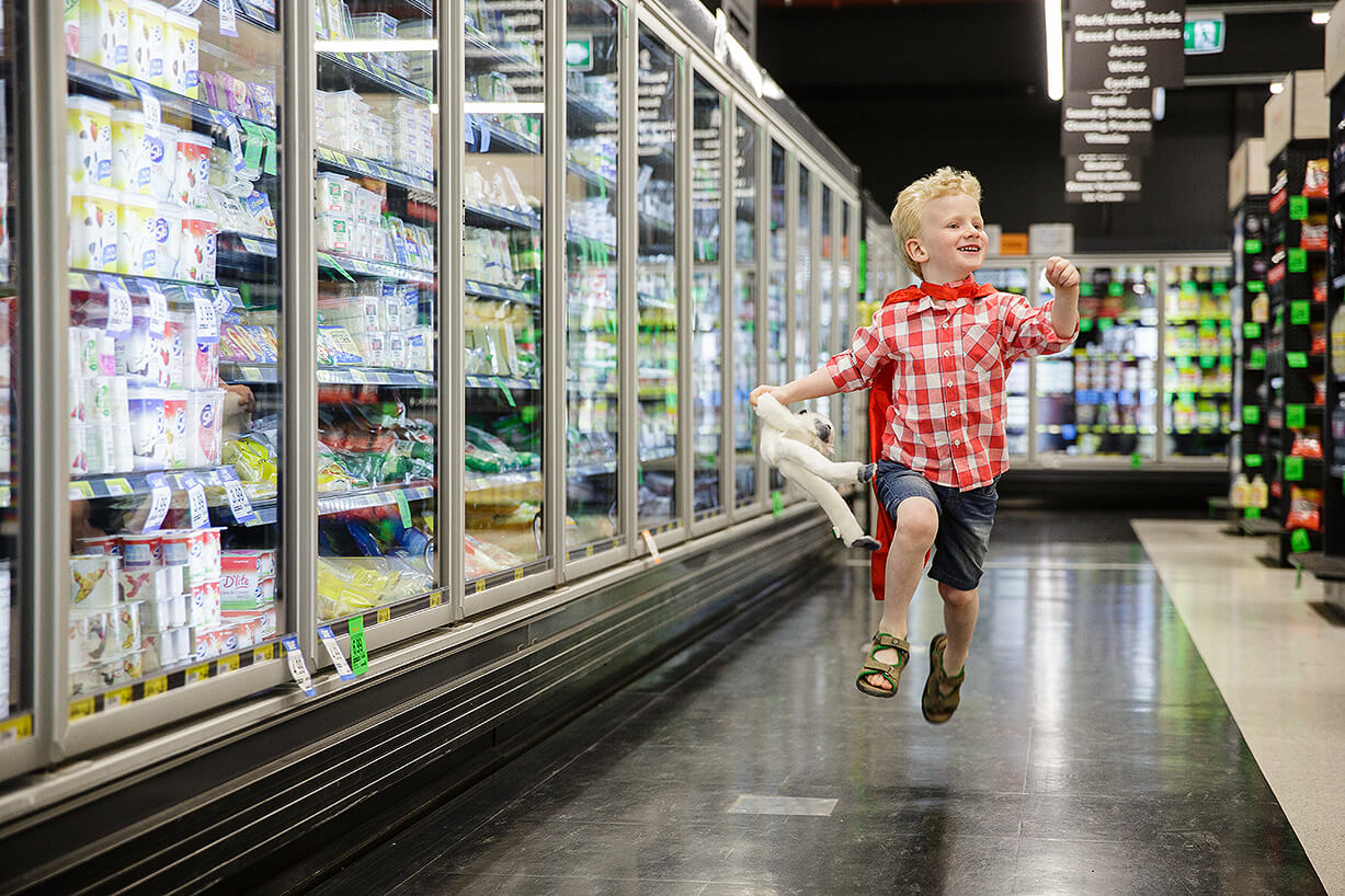 A young boy fly's through the frozen food section of a supermarket wearing a cape like superman