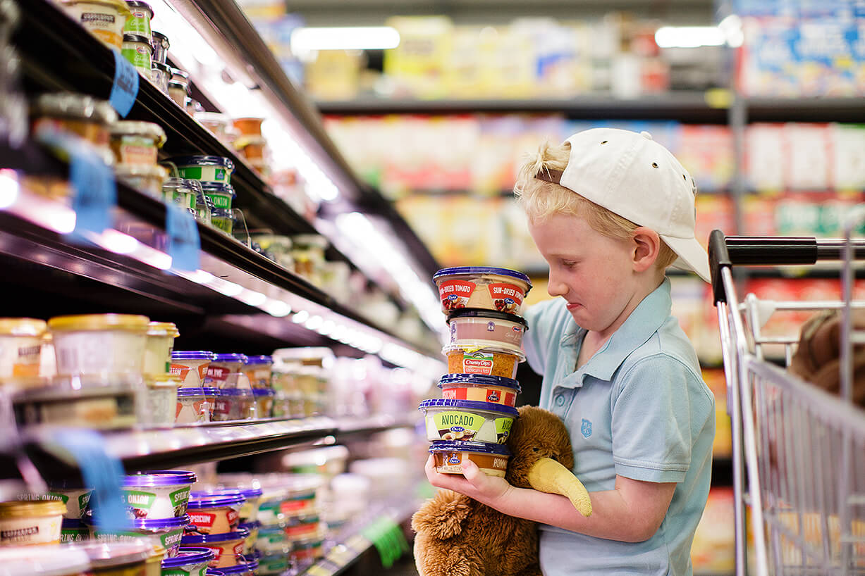 Retail food advertising photography of a boy in a supermarket stacking dips