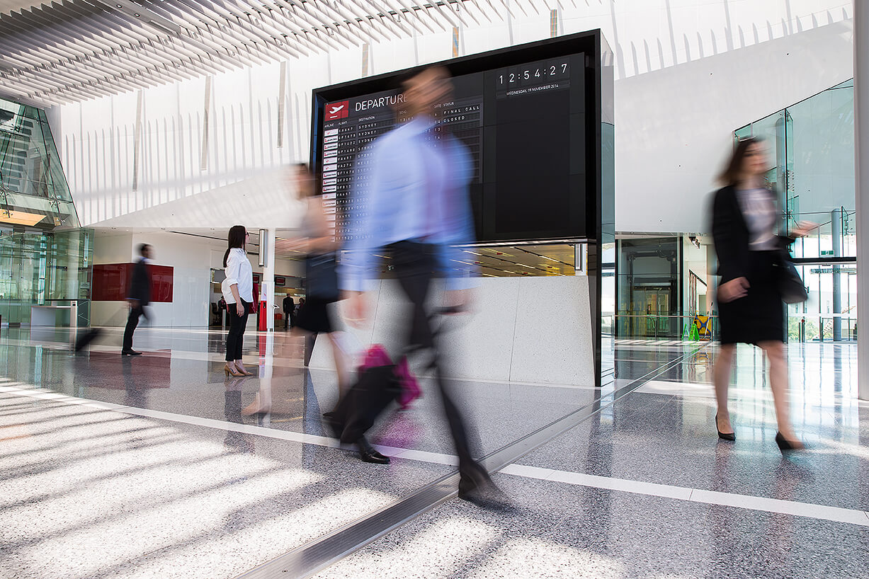 Busy modern airport architecture with travellers passing by with suitcases and wheelie bags showing a Qantas departure board Canberra Airport