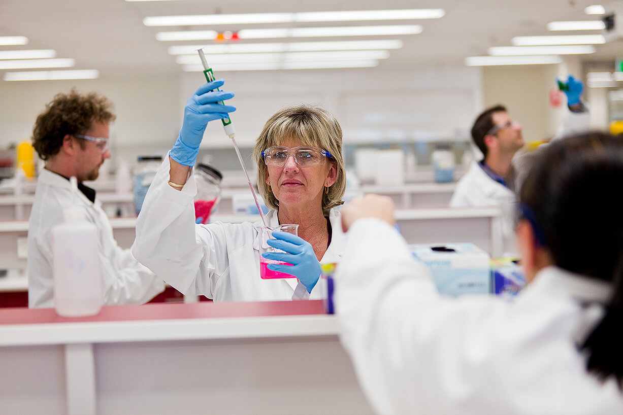 Scientists in white lab coats work in lab environment mixing liquids of colour