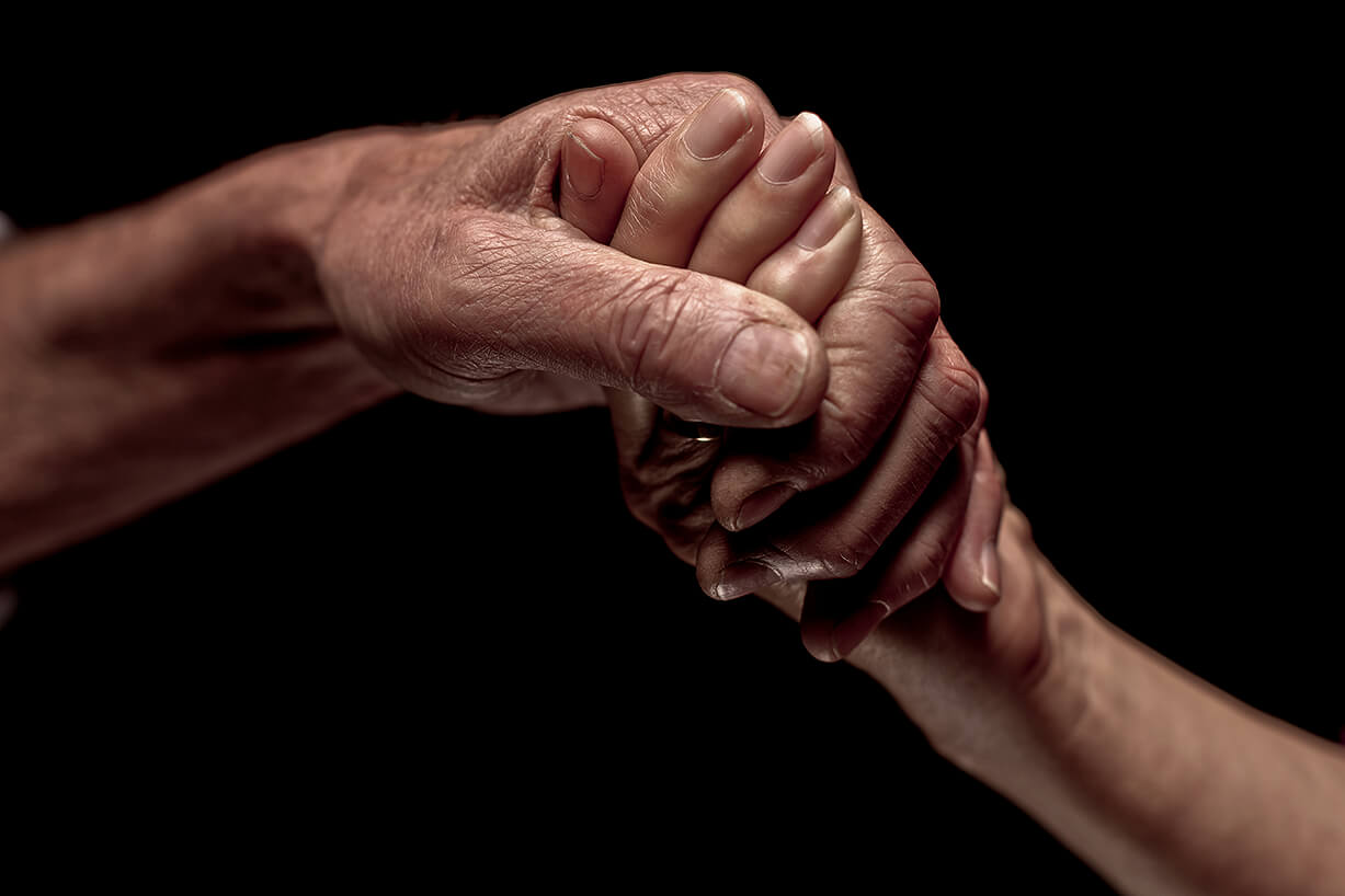An elderly hand with wrinkles holds a younger hand in a show of affection and family unity