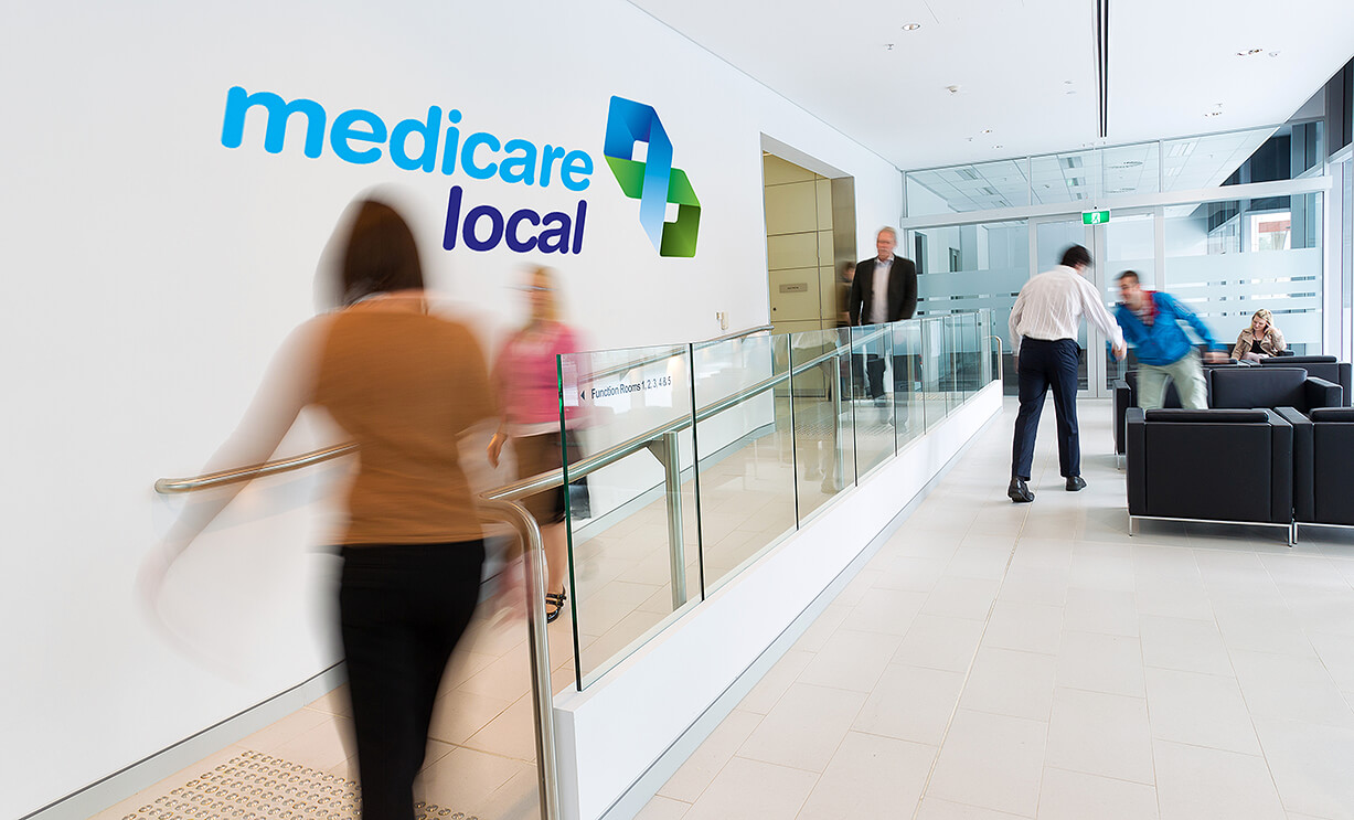 Medicare Local shop office space showing people moving around and Australian Government sign