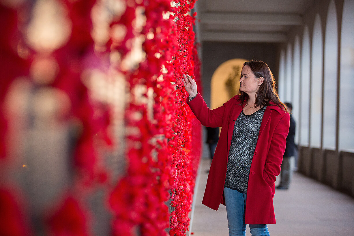 A person places a poppie on the wall of remembrance at the Australian War Memorial in Canberra