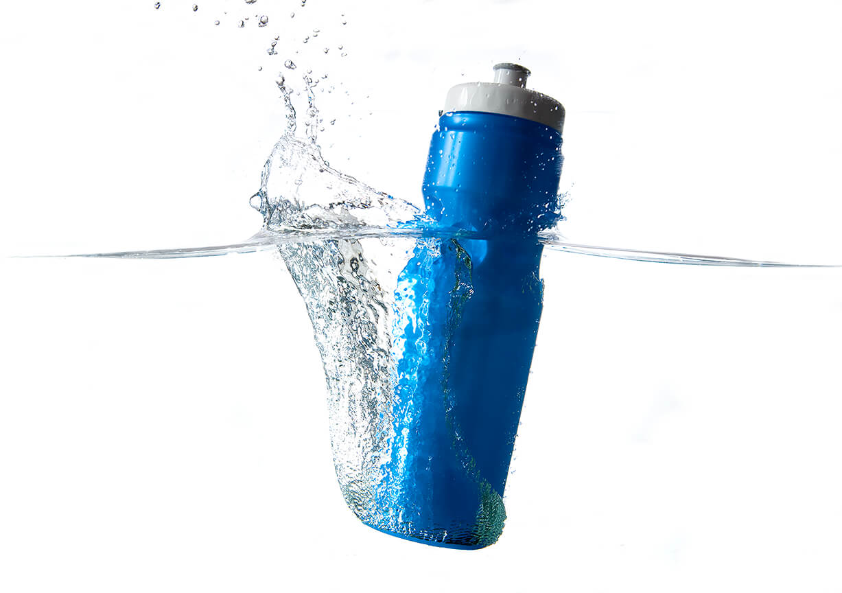 creative advertising product photograph of a water bottle dropping into water with water splash rising