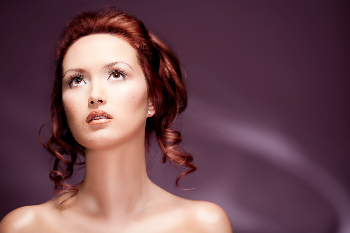 Beauty portrait photograph of red haired girl with flawless skin and long neck