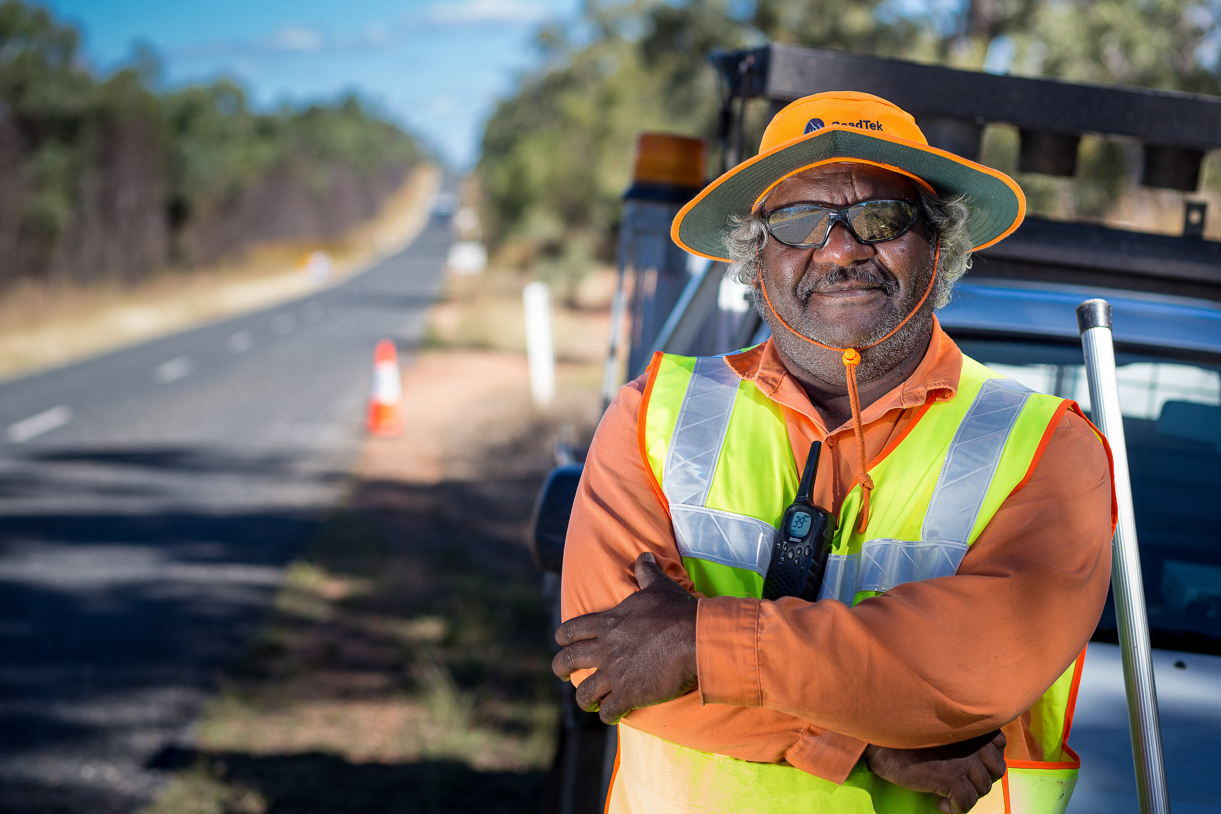 Portrait of an Indigenous Australian council worker working on the road wearing high visibility safety gear and sun protection